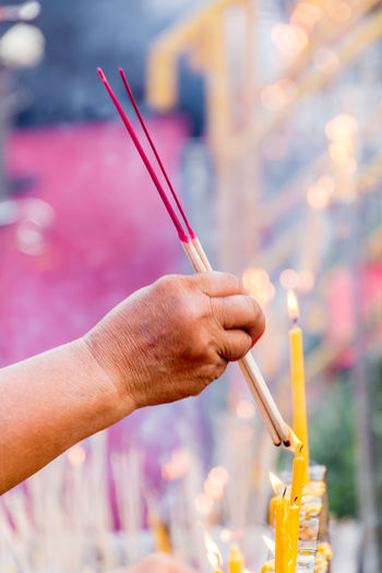 People are lighting incense stick to pray for goodness Buddhism; Burn; Candle; Close-up Culture; Day Fire; Focus On Foreground Goodness; Holding Human Body Part Human Hand Incense-sticks; Incense; Merit; One Person Outdoors People Pray; Real People Religion; Smell; Smoke; Stick - Plant Part Tradition;