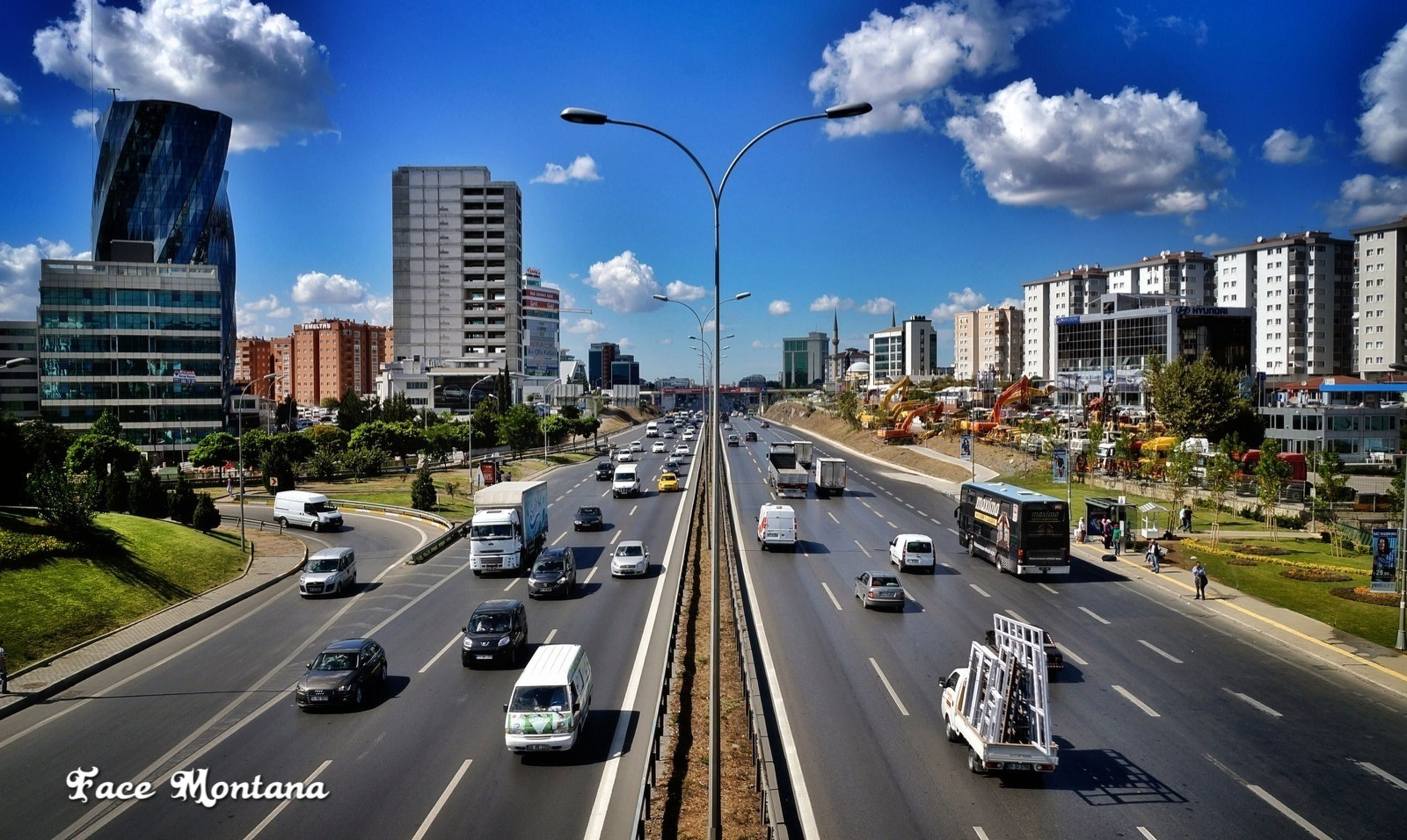 transportation, car, land vehicle, city, mode of transport, building exterior, architecture, built structure, road, traffic, street, road marking, high angle view, sky, city life, on the move, city street, skyscraper, highway, travel