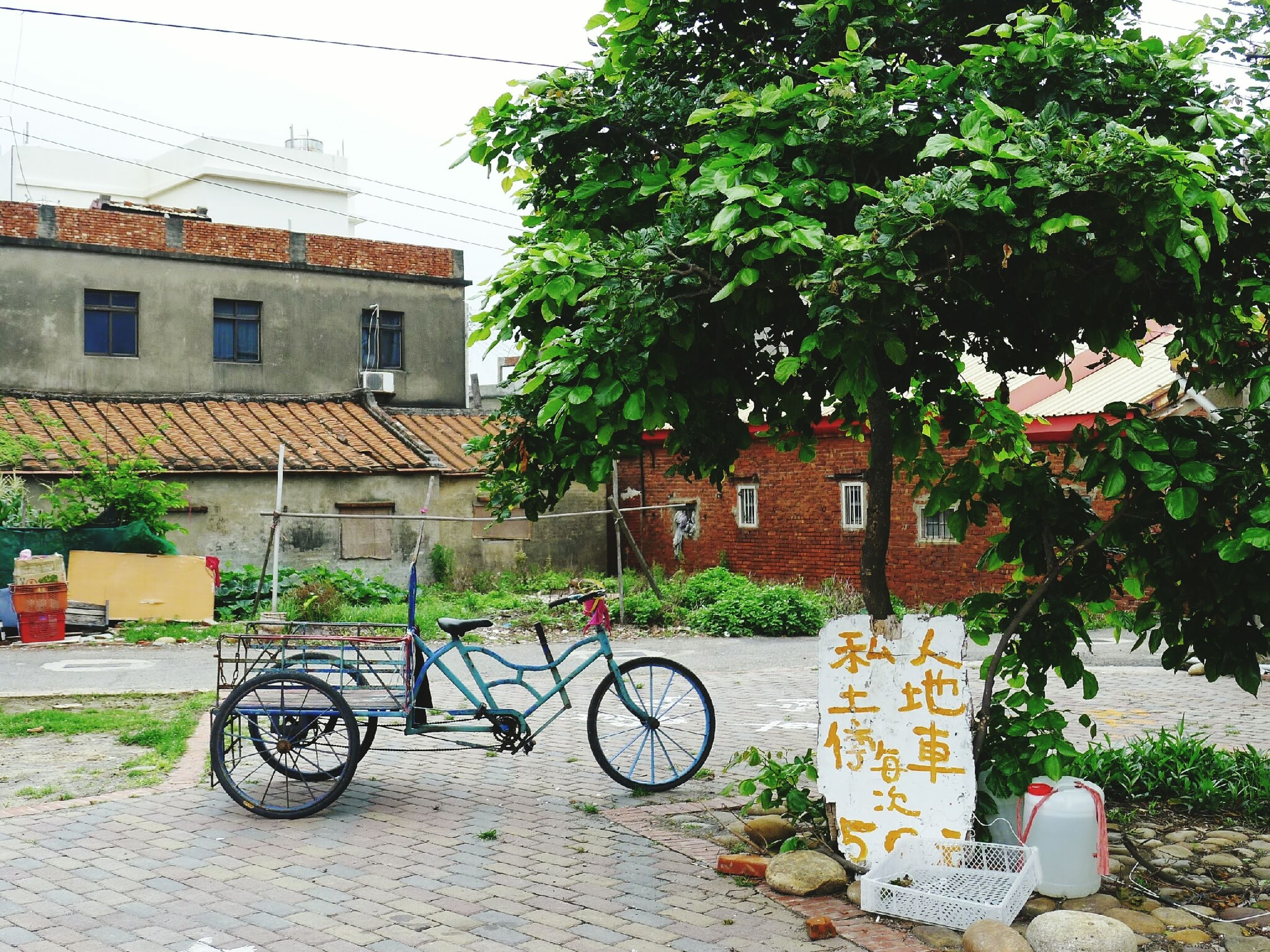 bicycle, building exterior, architecture, transportation, built structure, land vehicle, mode of transport, parked, stationary, parking, tree, house, street, residential structure, residential building, day, sidewalk, outdoors, cobblestone, city