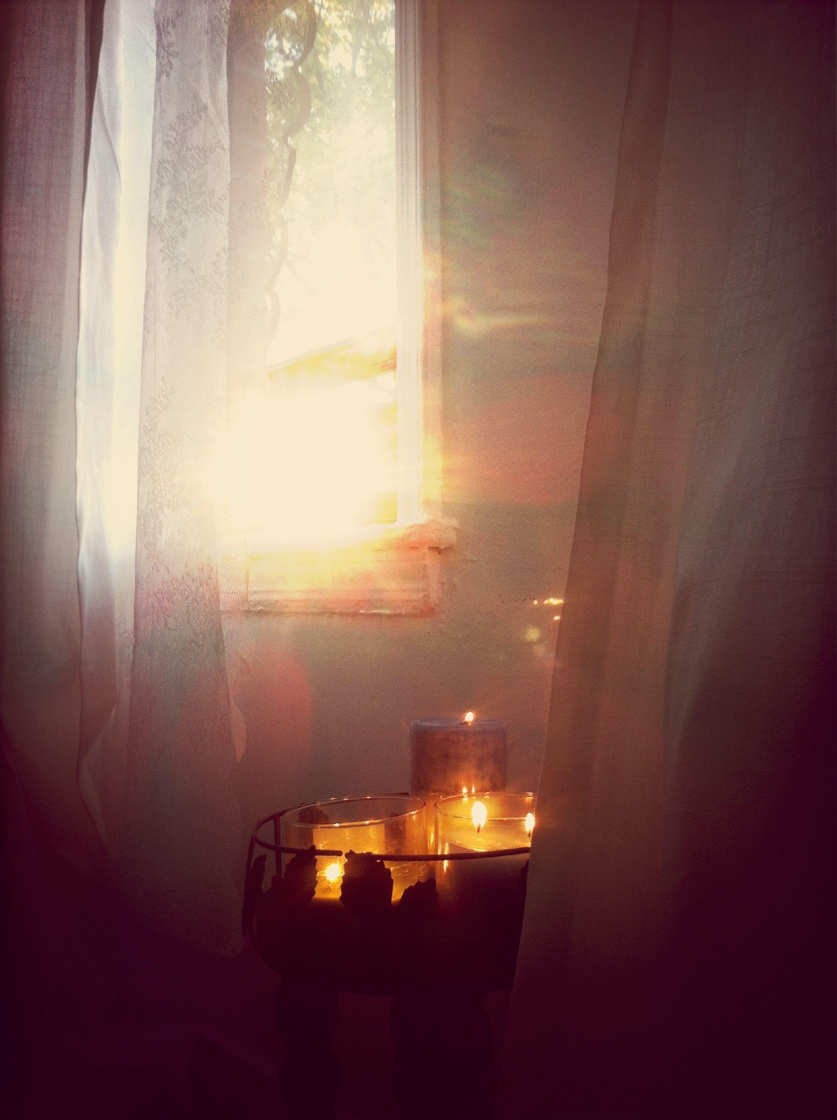 indoors, window, curtain, illuminated, glass - material, home interior, transparent, dark, lighting equipment, glowing, sunlight, light - natural phenomenon, house, sunbeam, no people, burning, reflection, flame, lit, darkroom