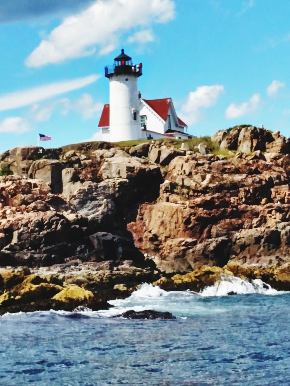 lighthouse, sky, guidance, water, direction, safety, sea, architecture, rock - object, waterfront, cliff, nature, blue, no people, built structure, beauty in nature, scenics, outdoors, day, building exterior