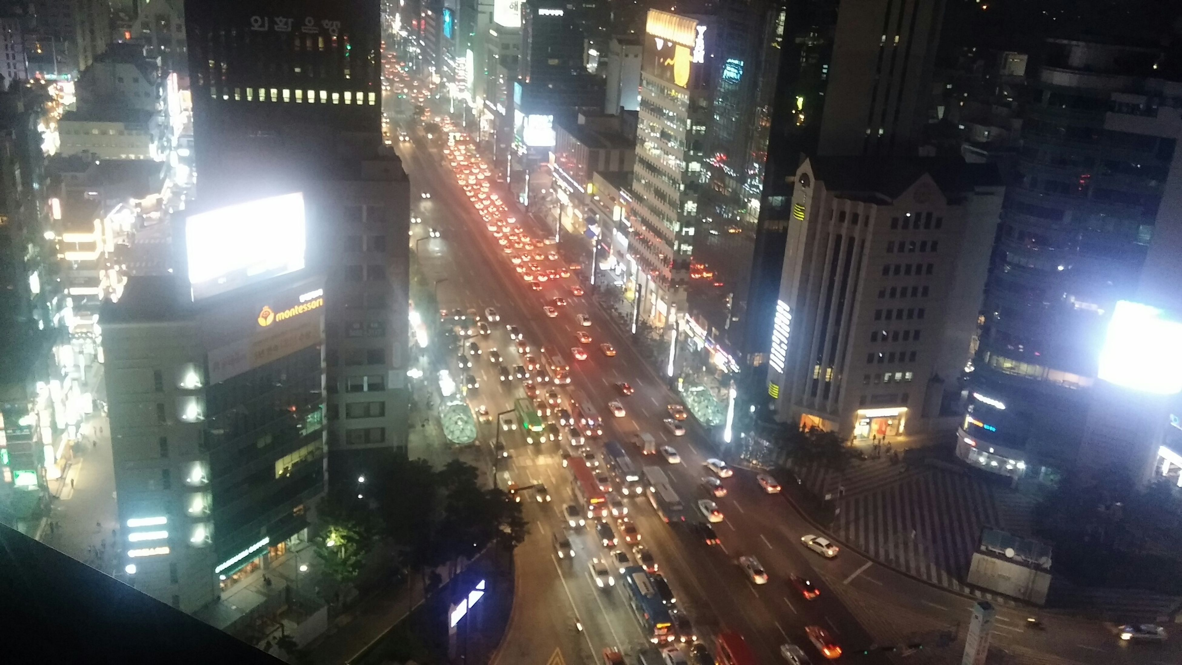 city, building exterior, architecture, illuminated, built structure, street, night, transportation, car, city street, city life, land vehicle, traffic, road, skyscraper, office building, high angle view, mode of transport, building, cityscape