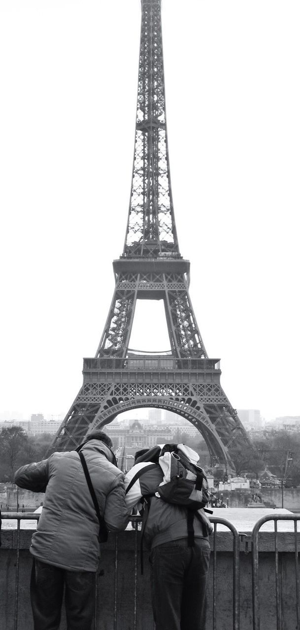 tower, travel destinations, international landmark, built structure, architecture, eiffel tower, tall - high, full length, famous place, tourism, person, casual clothing, culture, iron - metal, outdoors, skyscraper, history, sky, capital cities