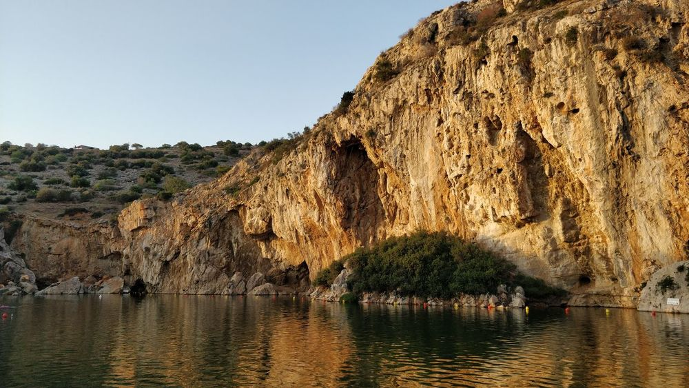 Greek Vouliagmeni Beauty In Nature Clear Sky Cliff Day Greece Lake Mountain Nature No People Outdoors Physical Geography Rock - Object Rock Formation Scenics Sky Tranquil Scene Tranquility Water Waterfront