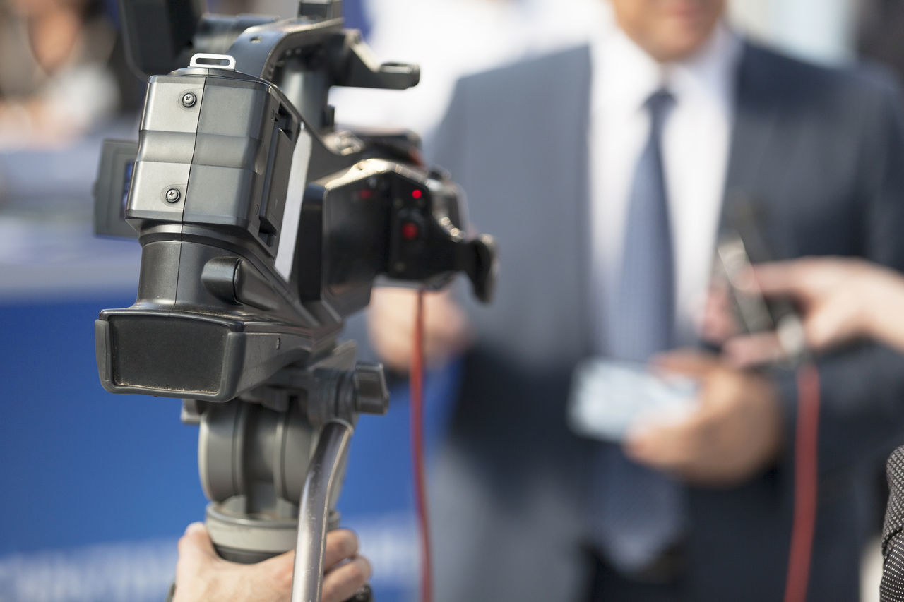 Filming an event with a video camera Adult Audio Business Businessman Camera - Photographic Equipment Camerman Close-up Covering Event Filming Hand Holding Journalist Journalist Media Interview Men Microphone Outdoors People Politician Television Television Camera Video Camera