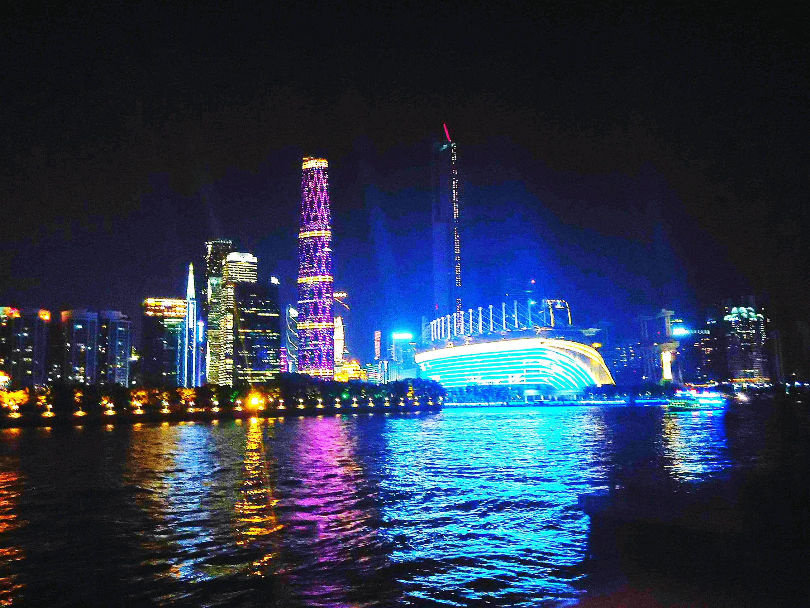 illuminated, night, water, building exterior, waterfront, architecture, built structure, city, reflection, river, sky, tall - high, skyscraper, sea, cityscape, tower, outdoors, city life, lighting equipment, modern