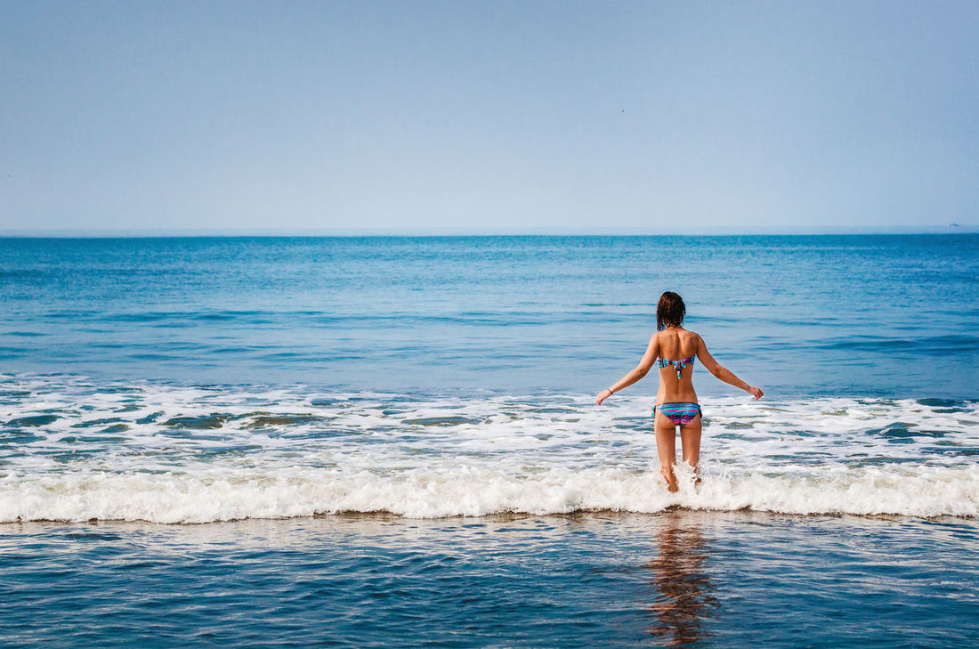 Girl standing in the ocean and looking at the horizon Beauty In Nature Bikini Enjoyment Girl Goa Horizon Over Water Idyllic India Lifestyles Nature People Of The Oceans Sea Seascape Shore Swimming Tranquil Scene Vacations Watching Water Wave Woman Feel The Journey People And Places