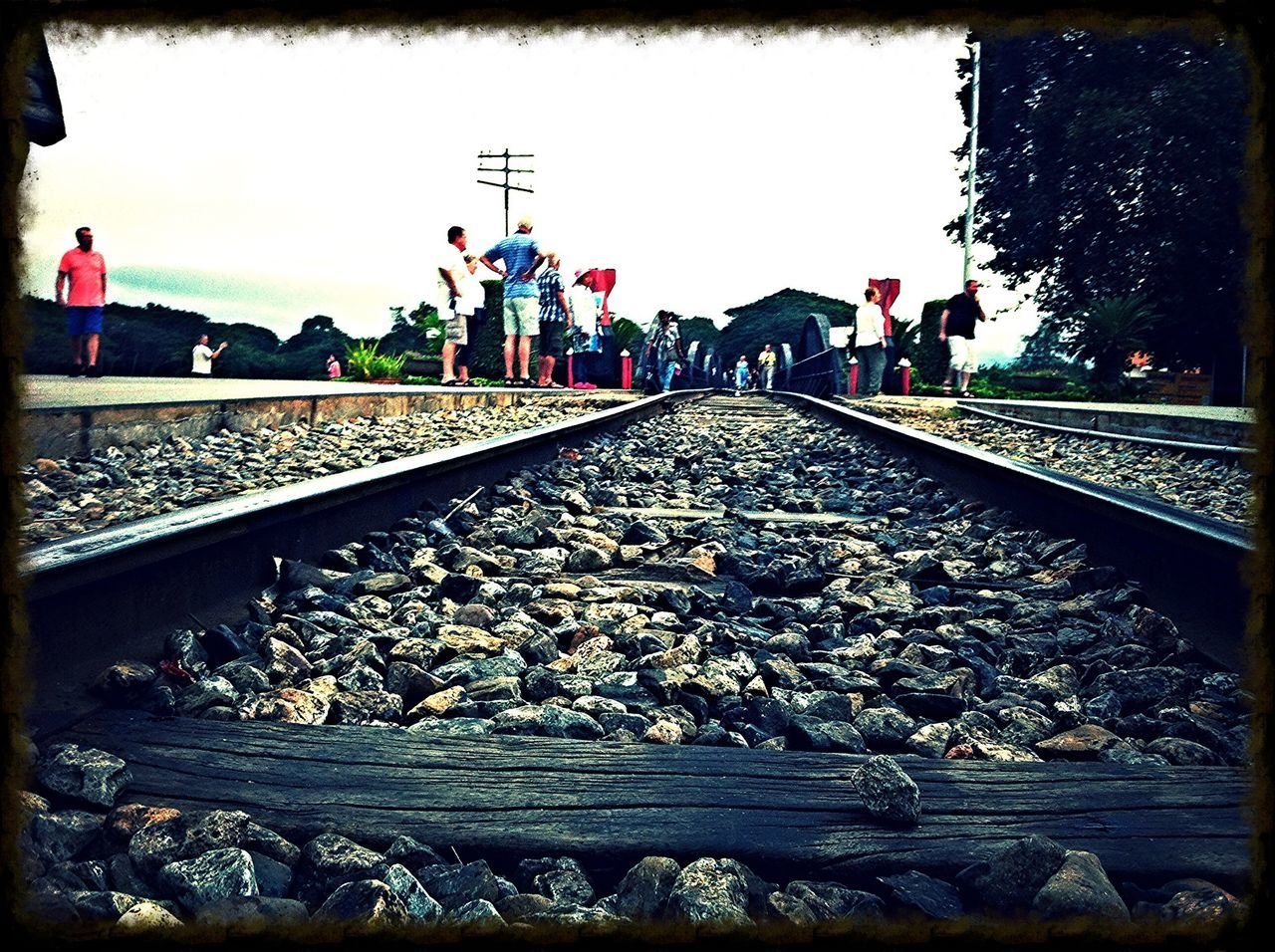railroad track, rail transportation, day, real people, large group of people, transportation, outdoors, men, women, standing, full length, sky, nature, adult, people