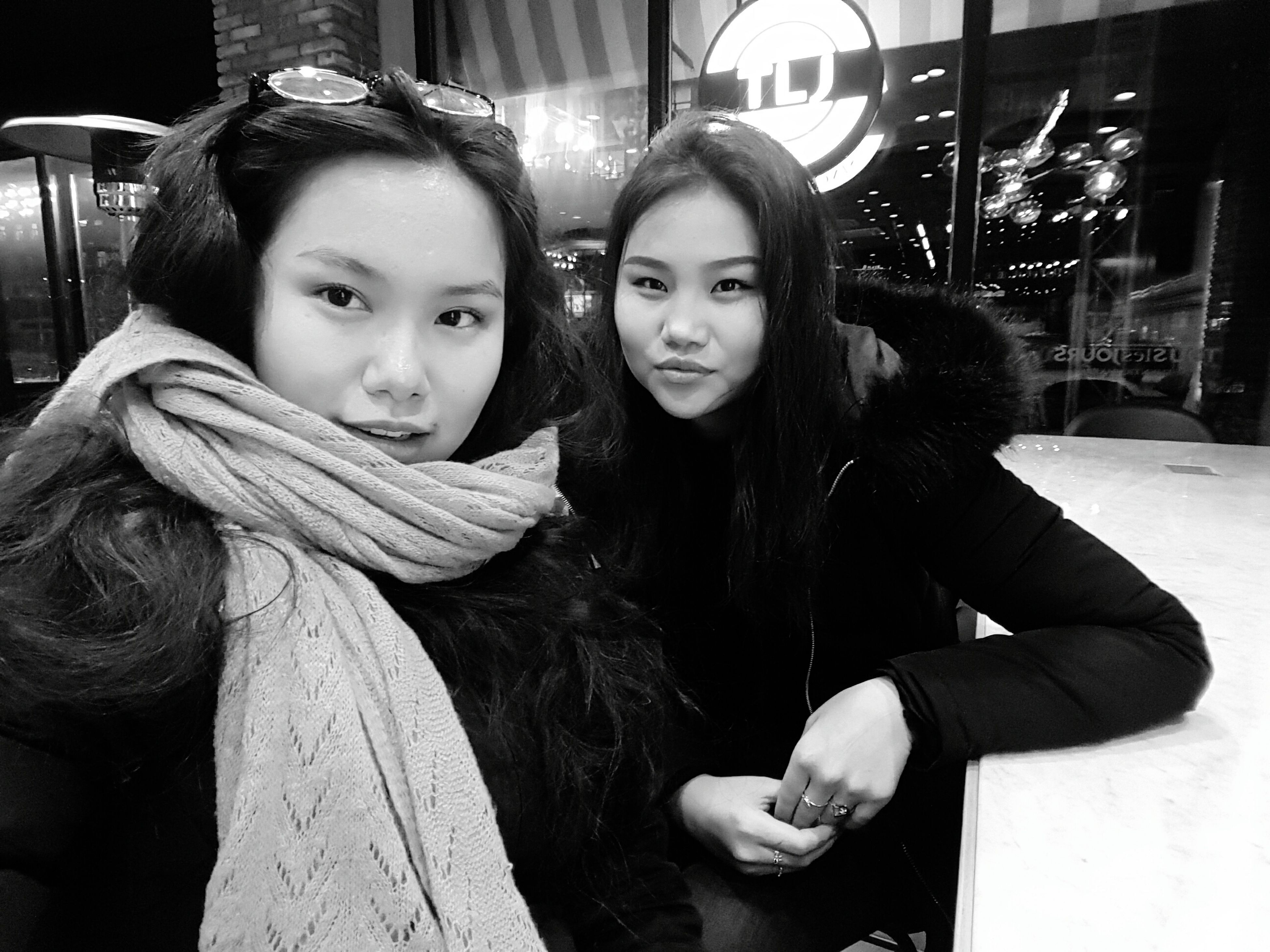 two people, looking at camera, portrait, night, young women, young adult, friendship, smiling, togetherness, embracing, sitting, lifestyles, beautiful people, happiness, women, city, bonding, adult, cheerful, christmas, real people, warm clothing, indoors, beautiful woman, people, adults only, hugging