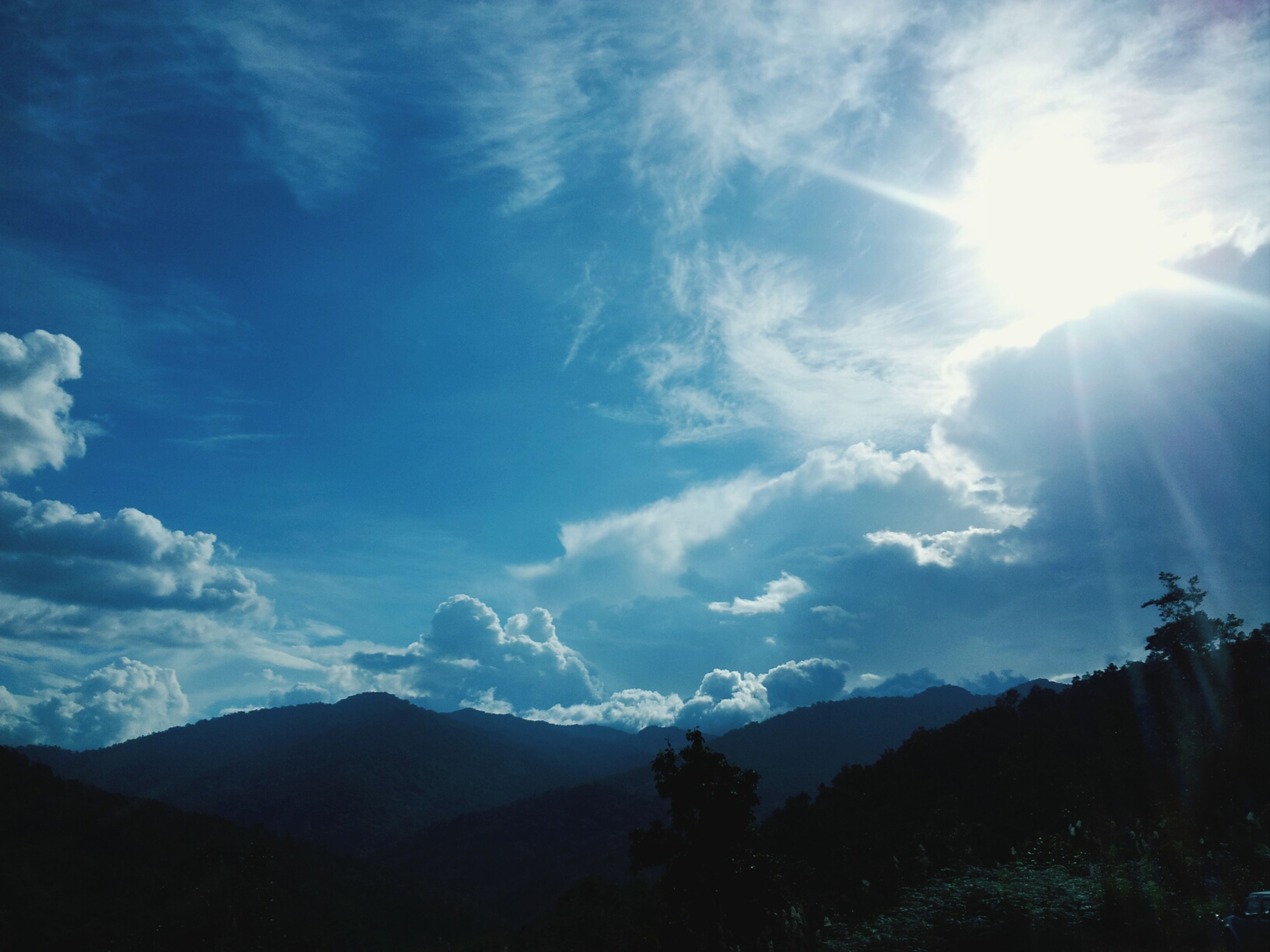 mountain, sun, sunbeam, tranquil scene, tranquility, scenics, beauty in nature, sky, mountain range, sunlight, nature, landscape, lens flare, cloud - sky, tree, silhouette, idyllic, non-urban scene, cloud, outdoors