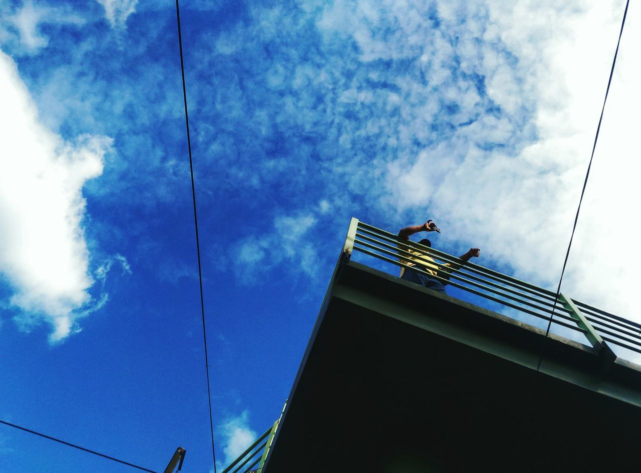 low angle view, cloud - sky, sky, cable, connection, day, architecture, built structure, blue, men, outdoors, one person, technology, one man only, people