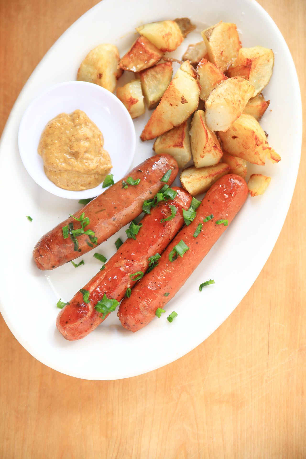 Sausages with scallions and potatoes Close-up Copy Space Delicious Dinner Fried Potatoes High Angle View Home Cooking Home Fries Home Fries Indoors  Lunch Meal Mustard Natural Light No People Platter Ready-to-eat Sausages Savory Food Scallions Table Vertical Wood Surface