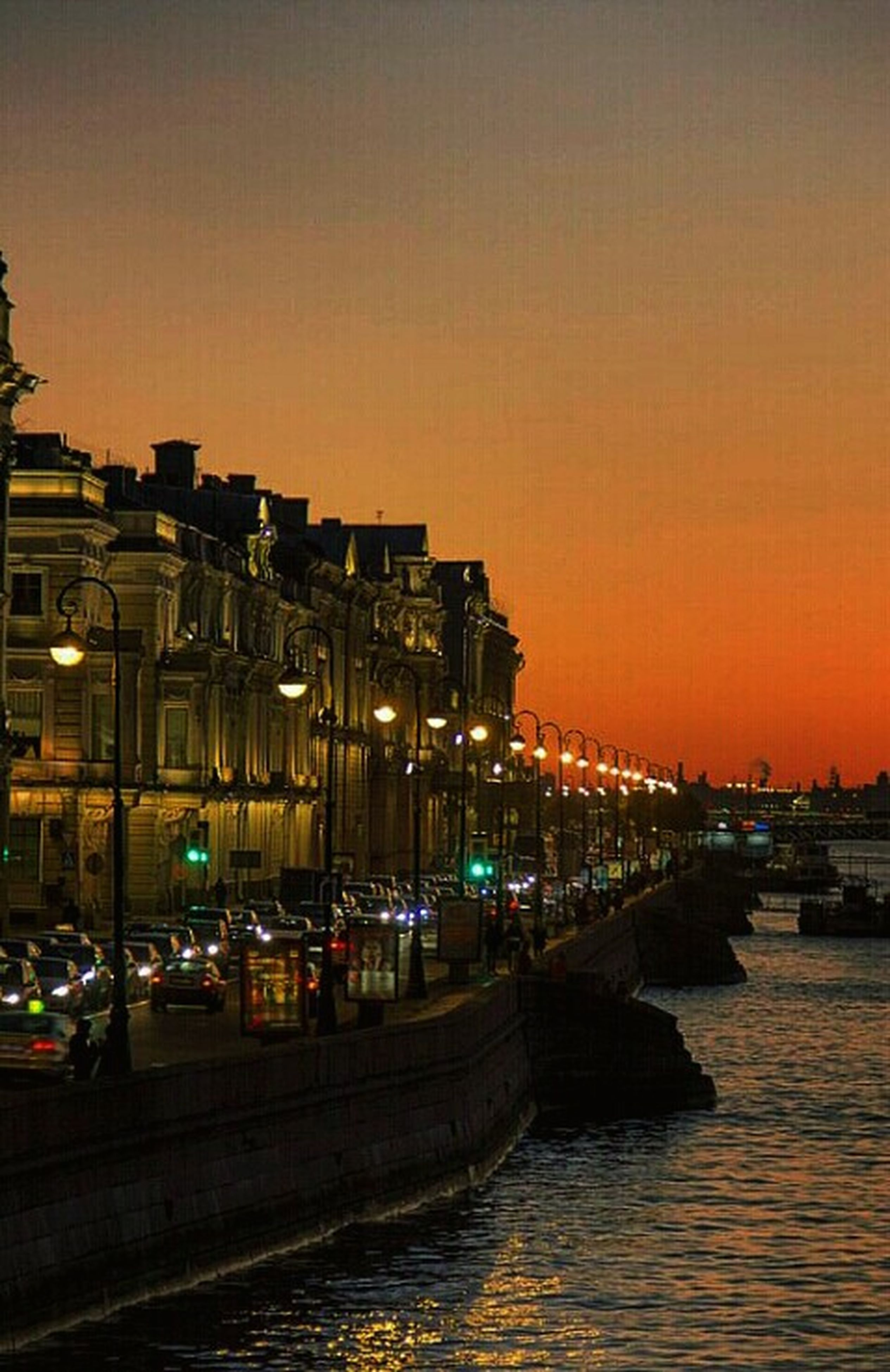 illuminated, building exterior, architecture, sunset, water, built structure, transportation, city, night, waterfront, orange color, sky, river, mode of transport, dusk, clear sky, reflection, outdoors, street light, sea