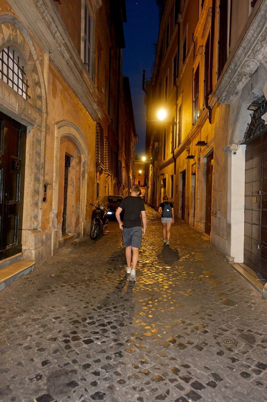 architecture, walking, built structure, full length, building exterior, rear view, real people, illuminated, the way forward, men, leisure activity, night, lifestyles, women, one person, outdoors, people
