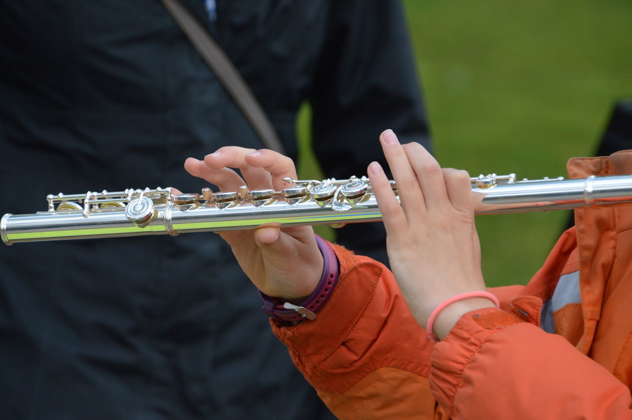 music, musical instrument, musician, wind instrument, arts culture and entertainment, playing, performance, skill, real people, woodwind instrument, marching band, midsection, outdoors, human hand, performing arts event, men, saxophone, day, classical music, close-up, jazz music, people