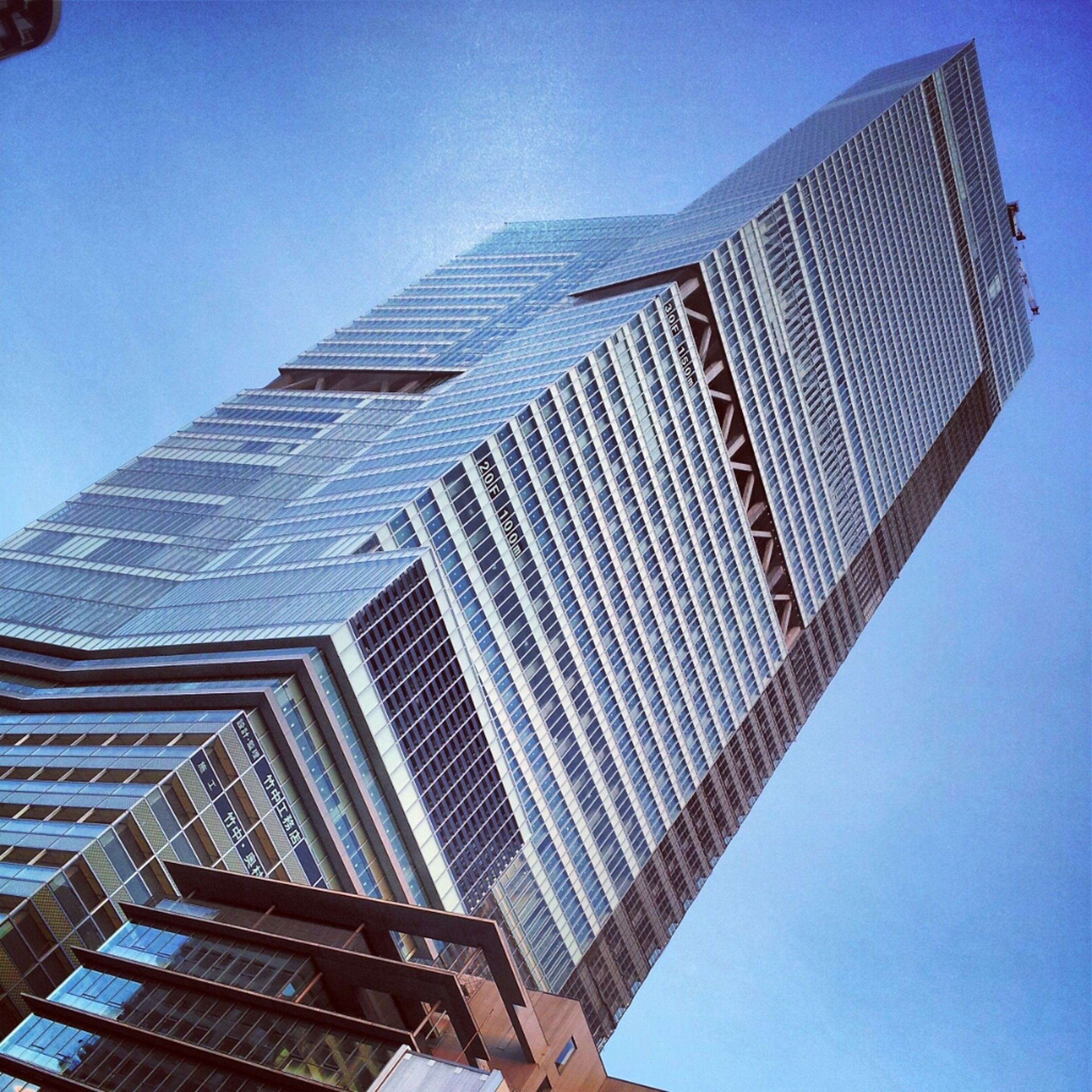 low angle view, architecture, built structure, building exterior, skyscraper, tall - high, modern, tower, office building, city, clear sky, blue, tall, capital cities, sky, famous place, travel destinations, building, day, no people
