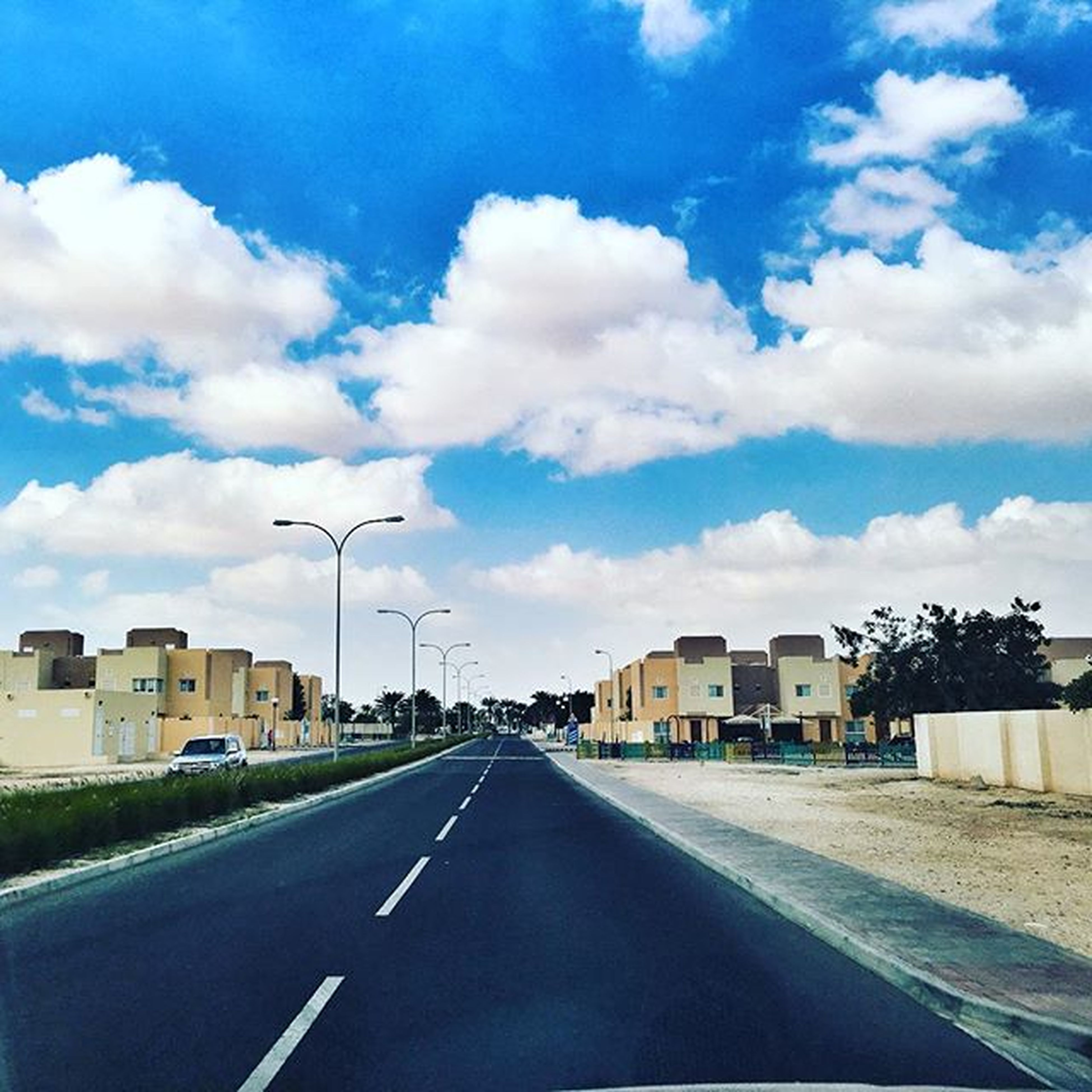 transportation, the way forward, road, sky, road marking, building exterior, diminishing perspective, built structure, vanishing point, architecture, street, cloud - sky, blue, car, cloud, mode of transport, empty, land vehicle, day, asphalt