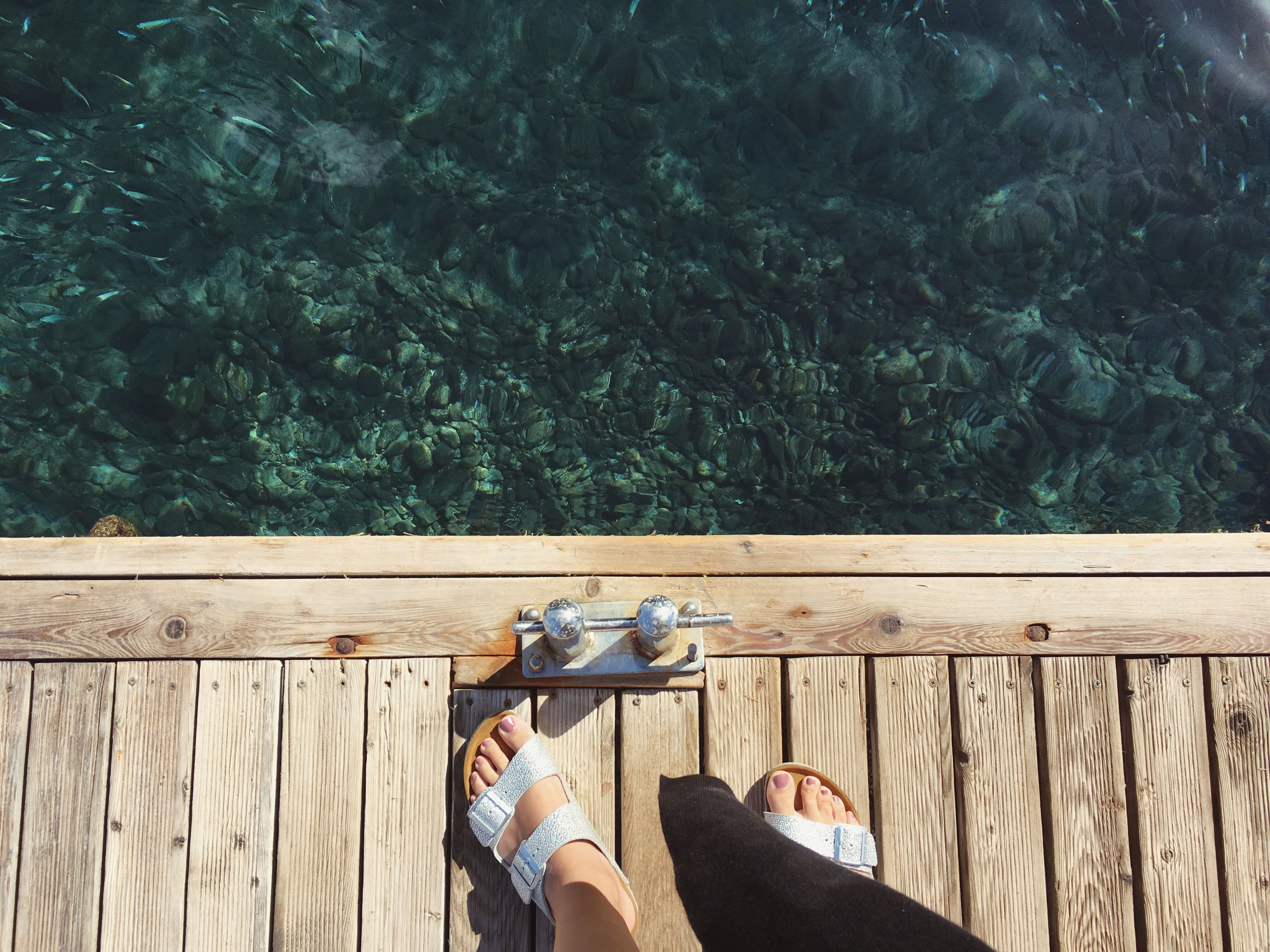 low section, person, railing, leisure activity, lifestyles, shoe, personal perspective, relaxation, human foot, blue, day, resting, outdoors