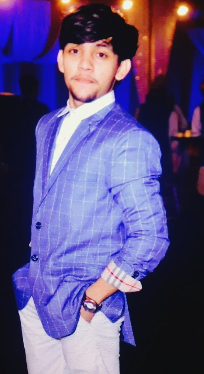 looking at camera, portrait, standing, three quarter length, one person, young adult, night, smiling, well-dressed, one young man only, indoors, illuminated, real people, one man only, people, adult, adults only