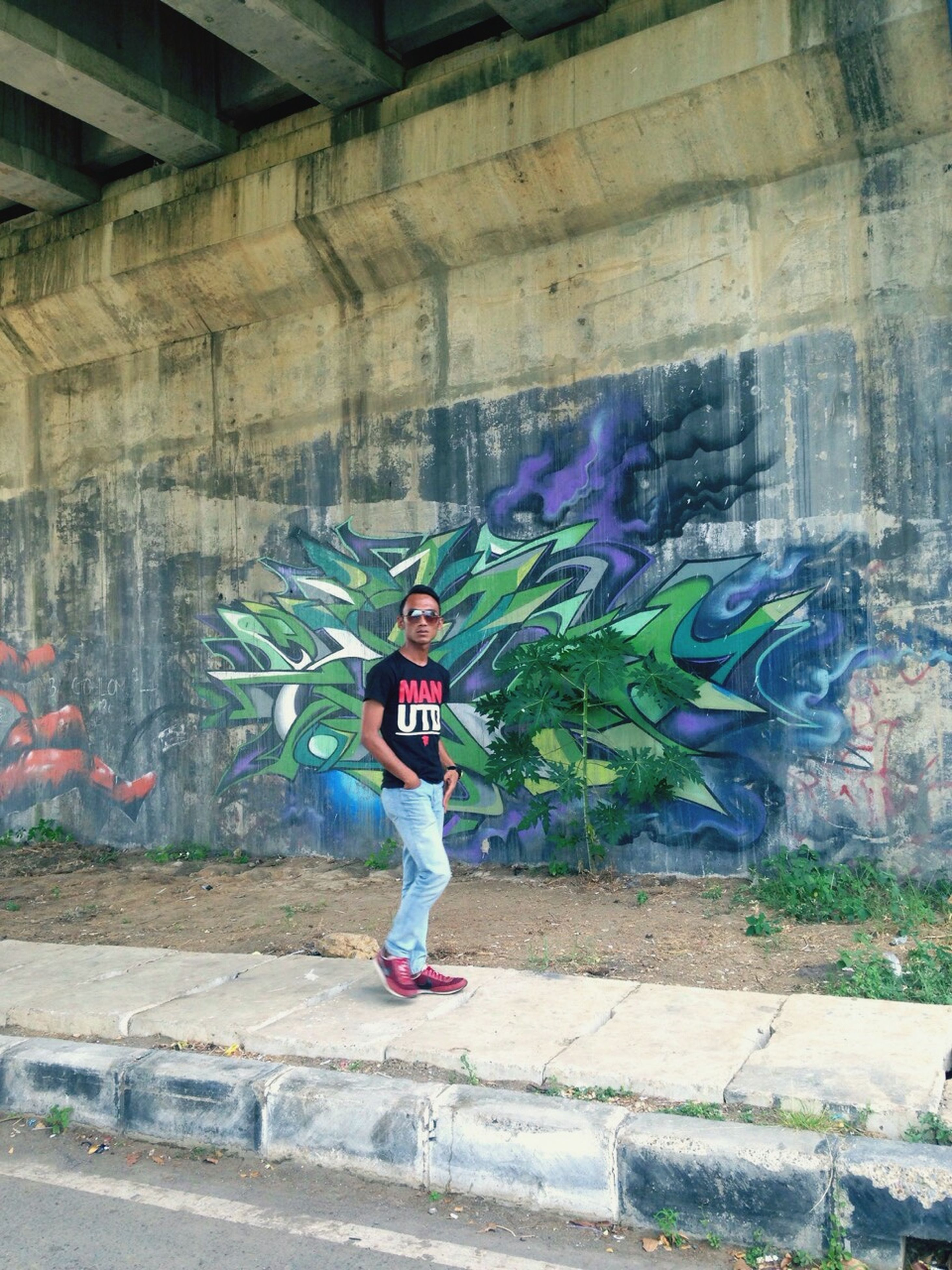 full length, graffiti, lifestyles, casual clothing, wall - building feature, person, built structure, architecture, leisure activity, front view, childhood, standing, building exterior, young adult, looking at camera, portrait, brick wall, art