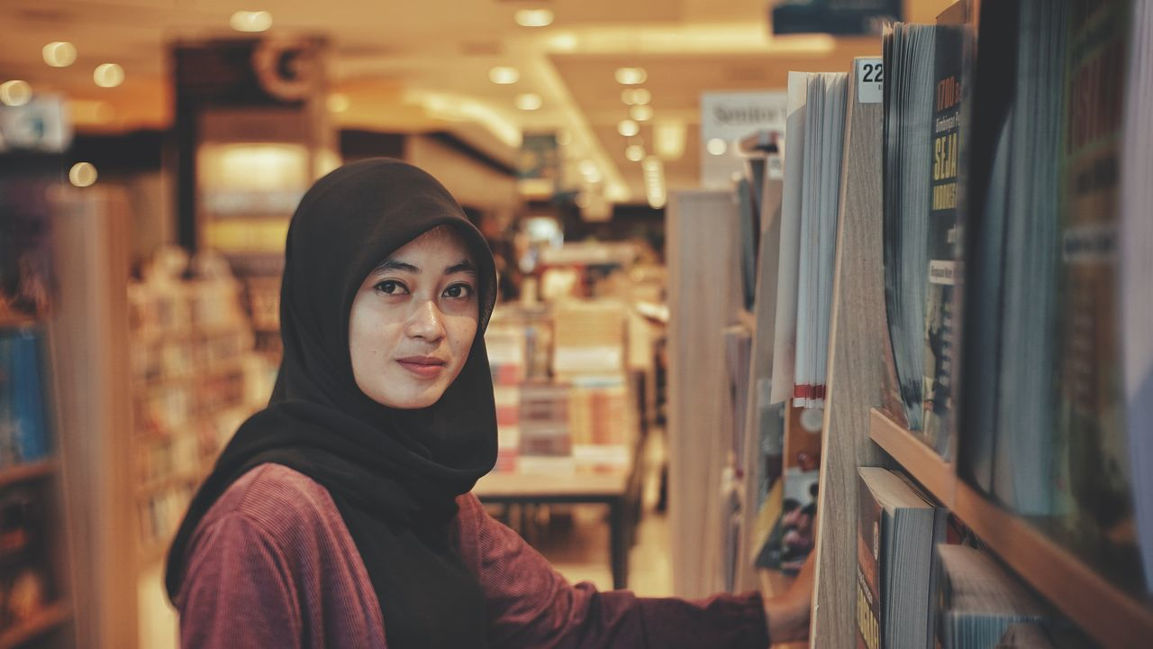looking at camera, portrait, one person, real people, indoors, focus on foreground, standing, front view, casual clothing, young women, lifestyles, leisure activity, young adult, library, smiling, day, bookshelf, close-up