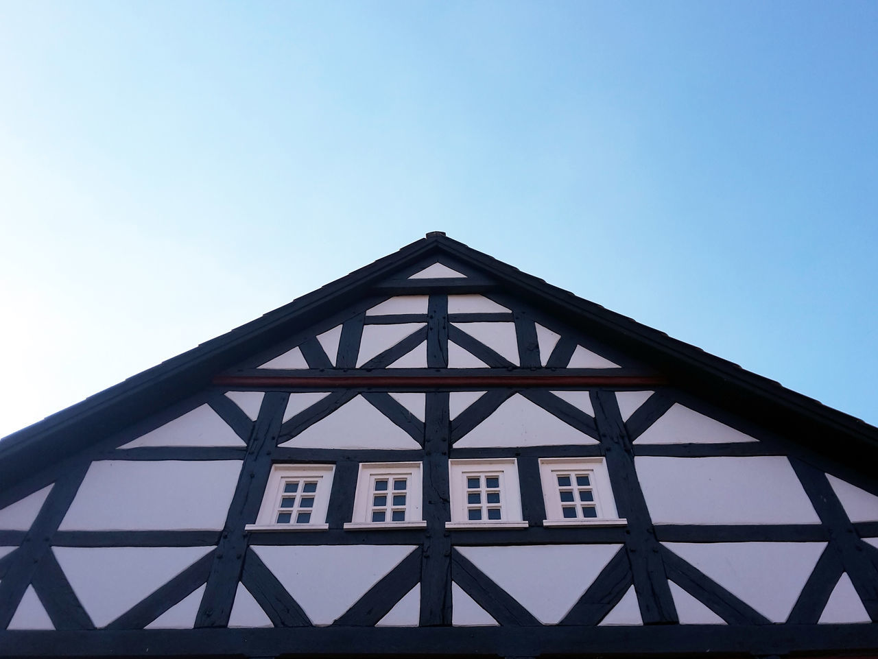 Front of old half-timbered house in late afternoon sun Architectural Feature Architecture Blue Blue Sky Building Exterior Built Structure Clear Sky Copy Space Day Façade Geometric Shape Half-timbered House High Section In Front Of Low Angle View No People Old House Outdoors Window