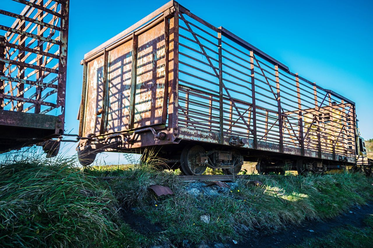 Low Angle View Of Abandoned Freight Train Against Clear Blue Sky