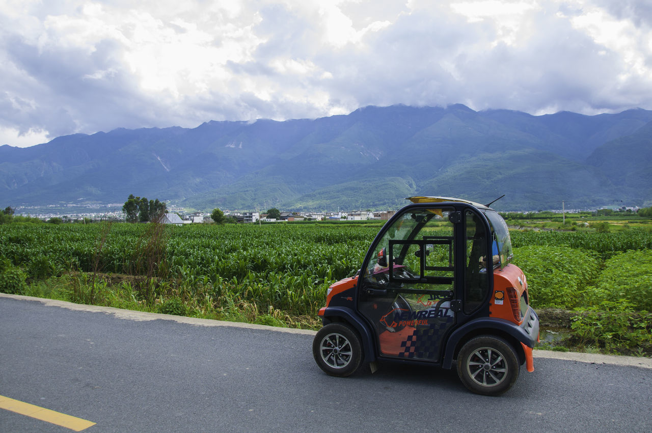 Small car on the road China Country Road Day Electric Car Field Grass Land Vehicle Landscape Lijiang Mountain No People Outdoors Road Sky Small Car Tiny Car Transportation Travel Destinations Travel Photography On The Way Showcase July EyeEmNewHere EyeEm Gallery EyeEm Best Shots