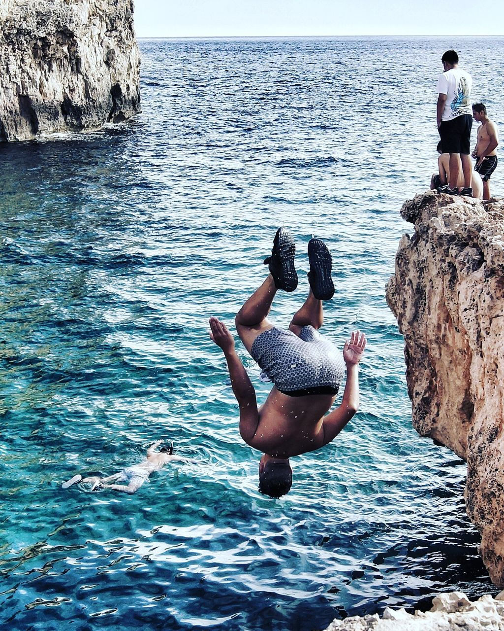 sea, real people, water, rock - object, men, lifestyles, leisure activity, beauty in nature, full length, nature, rear view, day, shirtless, horizon over water, outdoors, two people, scenics, togetherness, standing, clear sky, sky, adult, people