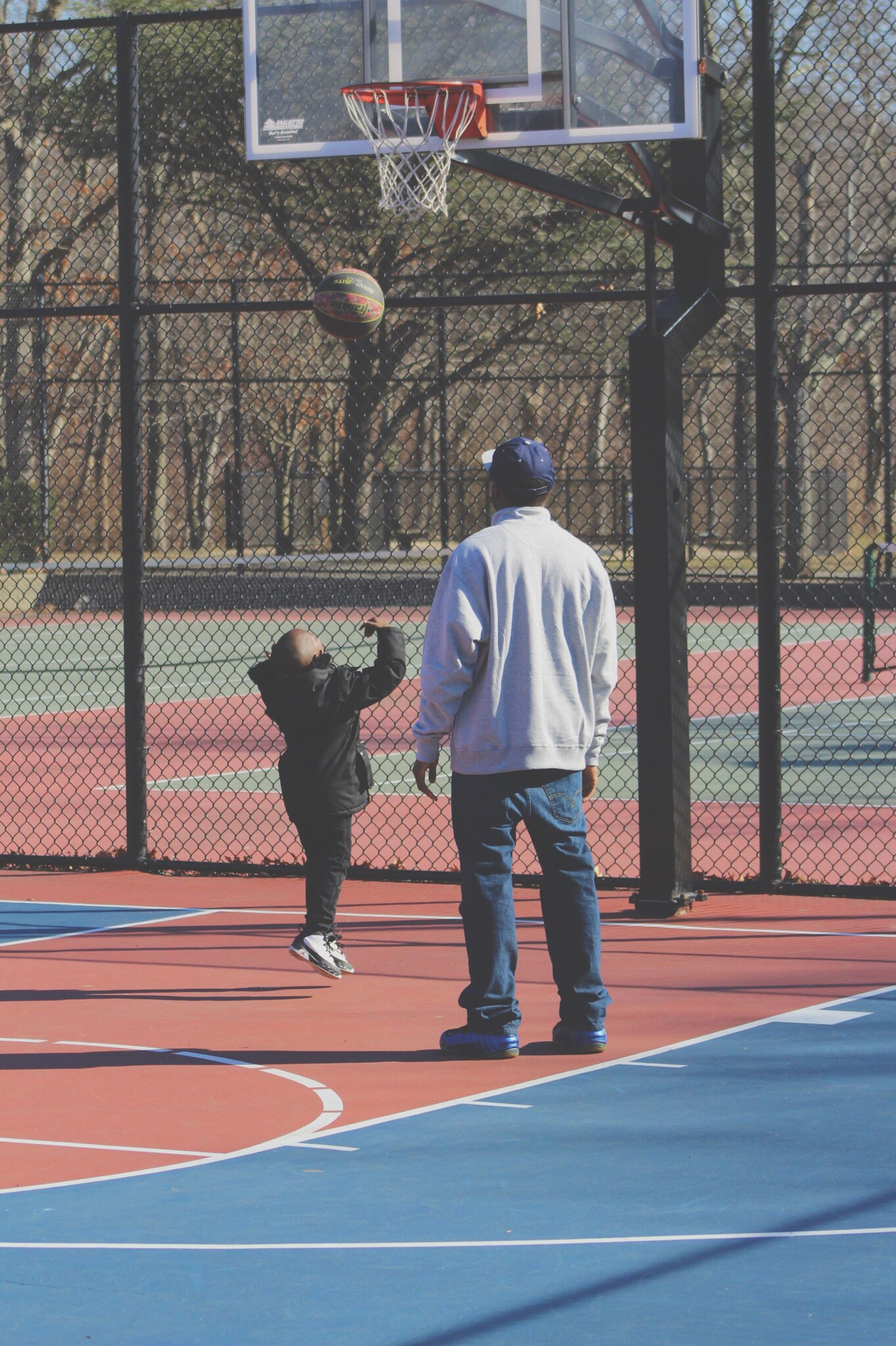 full length, two people, rear view, togetherness, leisure activity, court, outdoors, lifestyles, basketball - sport, day, men, sport, basketball hoop, real people, adult, people, taking a shot - sport