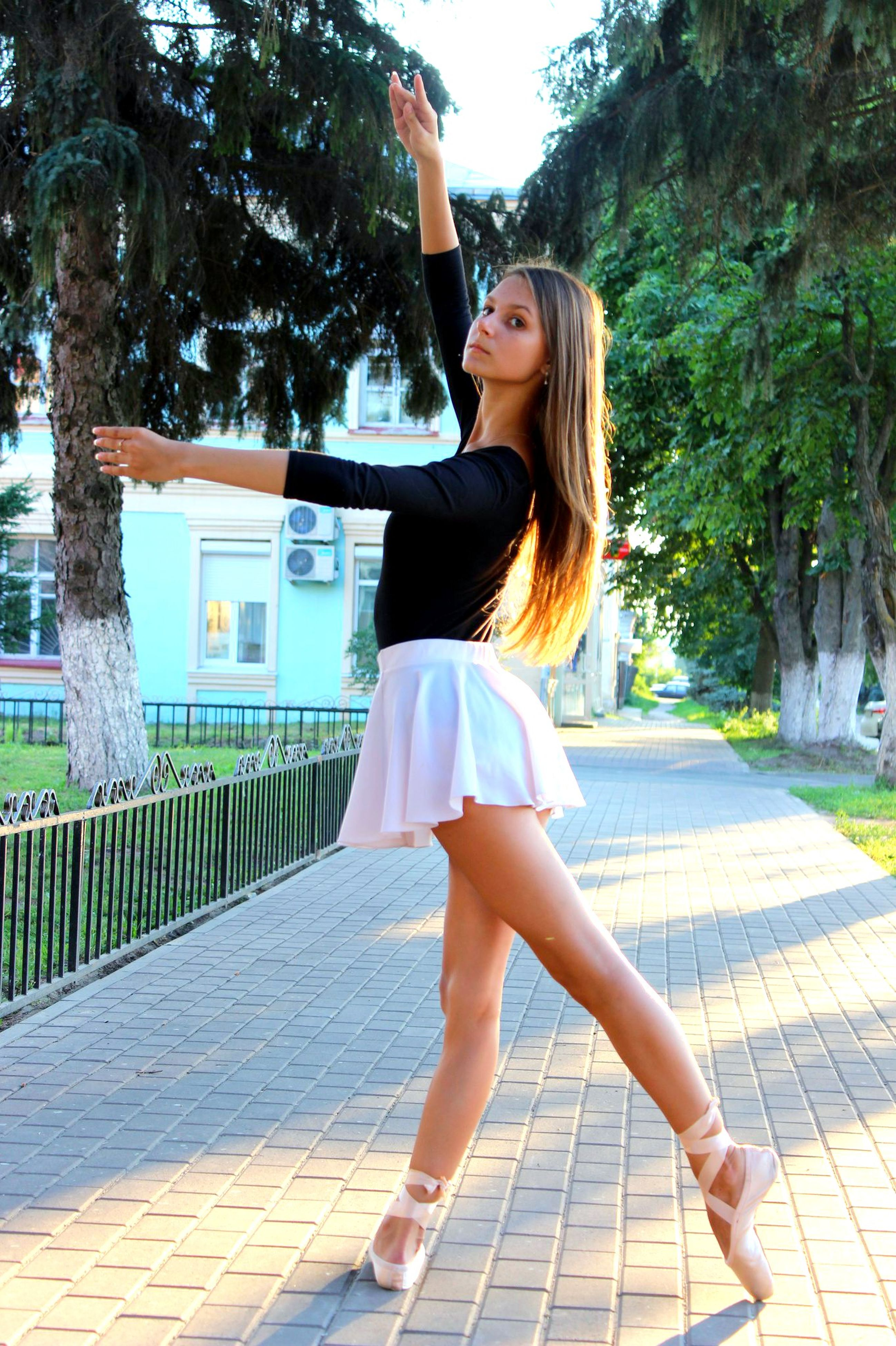 tree, lifestyles, full length, young adult, casual clothing, leisure activity, young women, person, long hair, standing, railing, dress, rear view, park - man made space, day, outdoors, side view