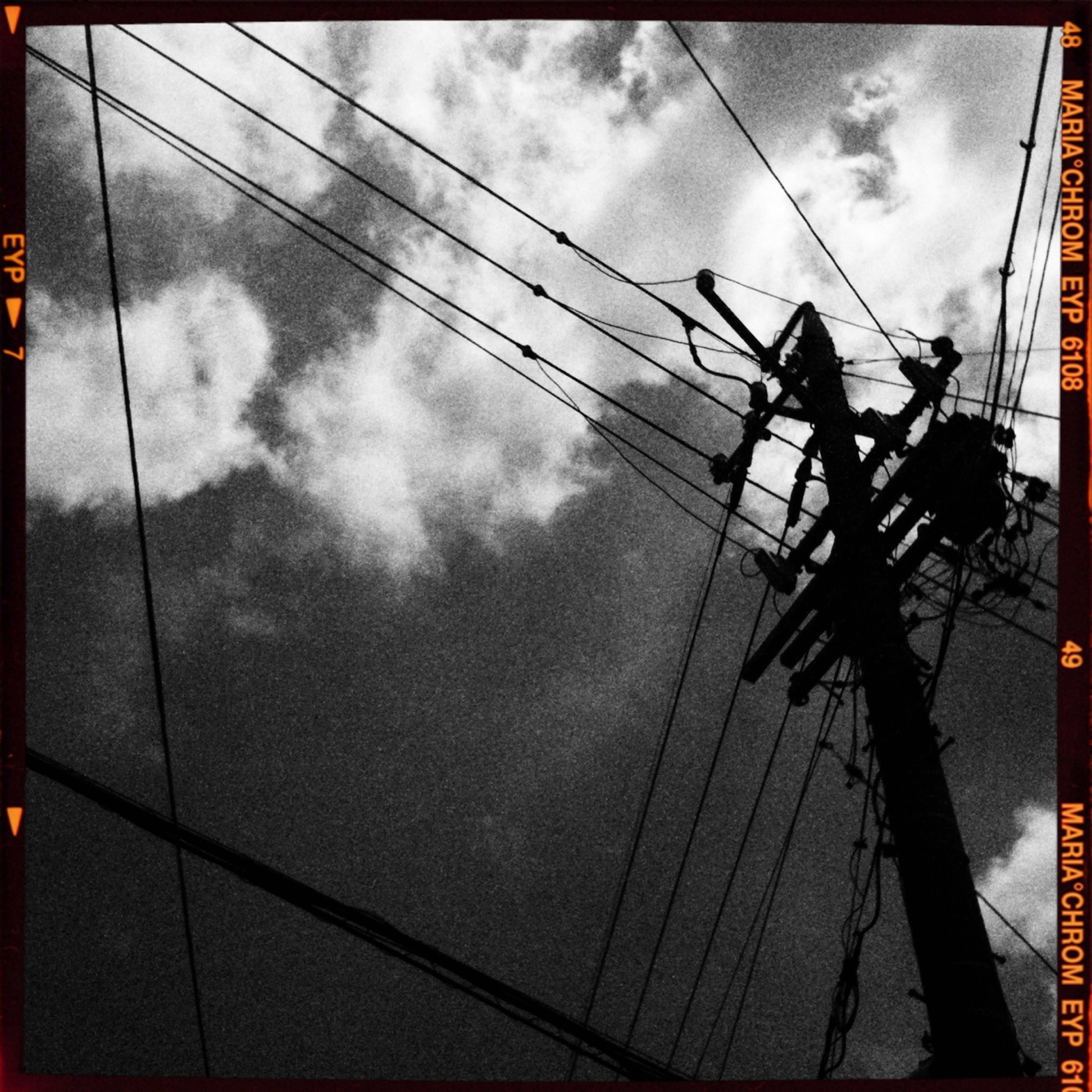 sky, cloud - sky, low angle view, power line, cloudy, electricity pylon, cable, connection, cloud, power supply, transportation, silhouette, built structure, transfer print, auto post production filter, electricity, architecture, weather, mode of transport, outdoors