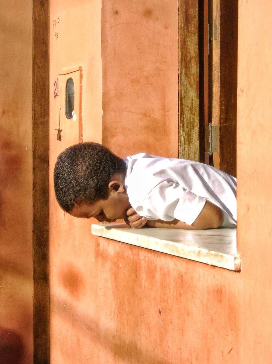 Curiosity Boy One Person Windowsill Wall Orange Orange Wall  Boy Looking Out Of A Window Curious Boy One Boy Childhood Sunny Facade