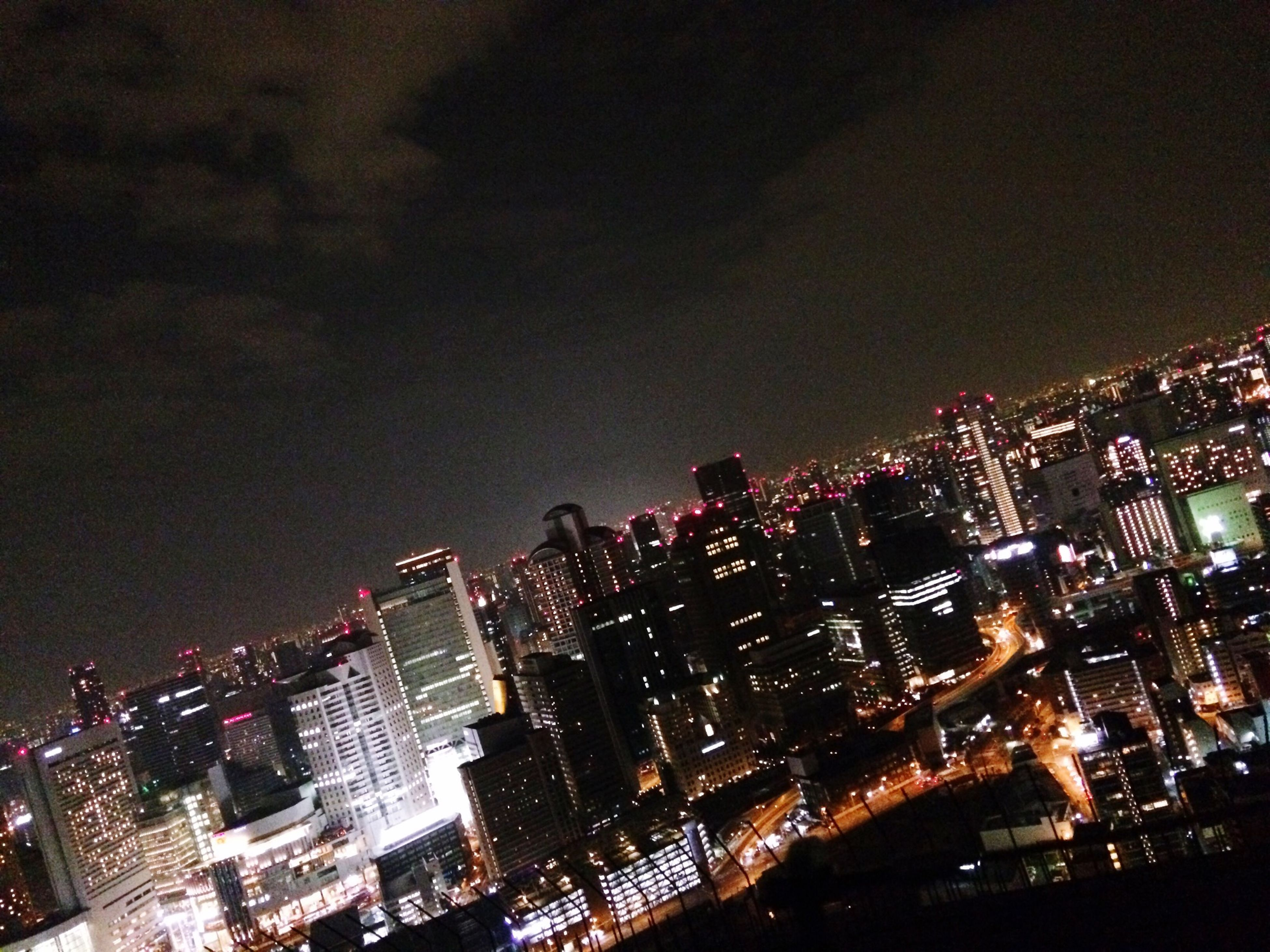 night, illuminated, city, building exterior, architecture, cityscape, built structure, skyscraper, modern, sky, tall - high, tower, office building, crowded, urban skyline, city life, financial district, high angle view, residential building, capital cities