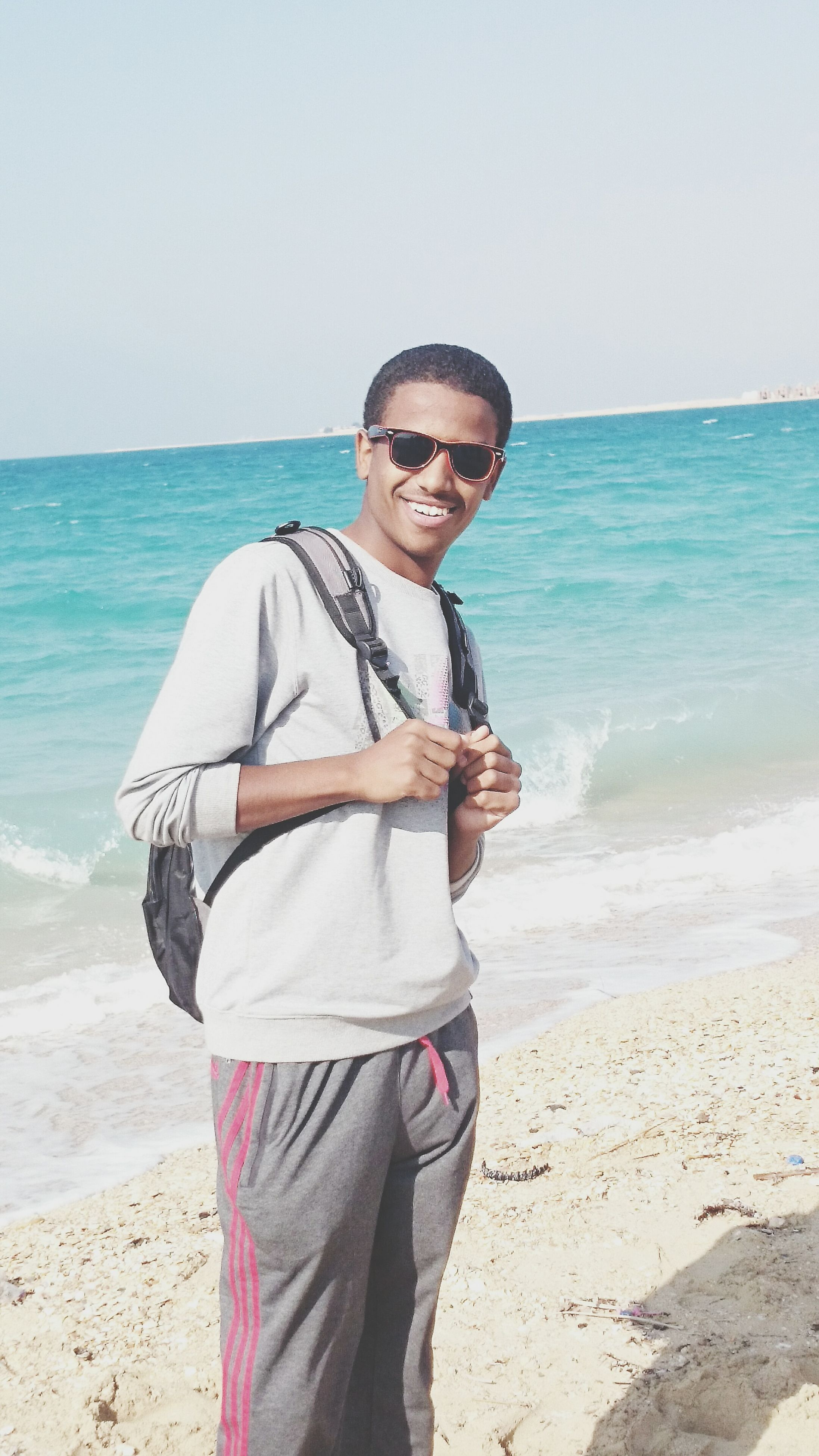 sea, beach, young adult, lifestyles, person, casual clothing, water, horizon over water, shore, portrait, looking at camera, leisure activity, standing, sunglasses, clear sky, young men, front view