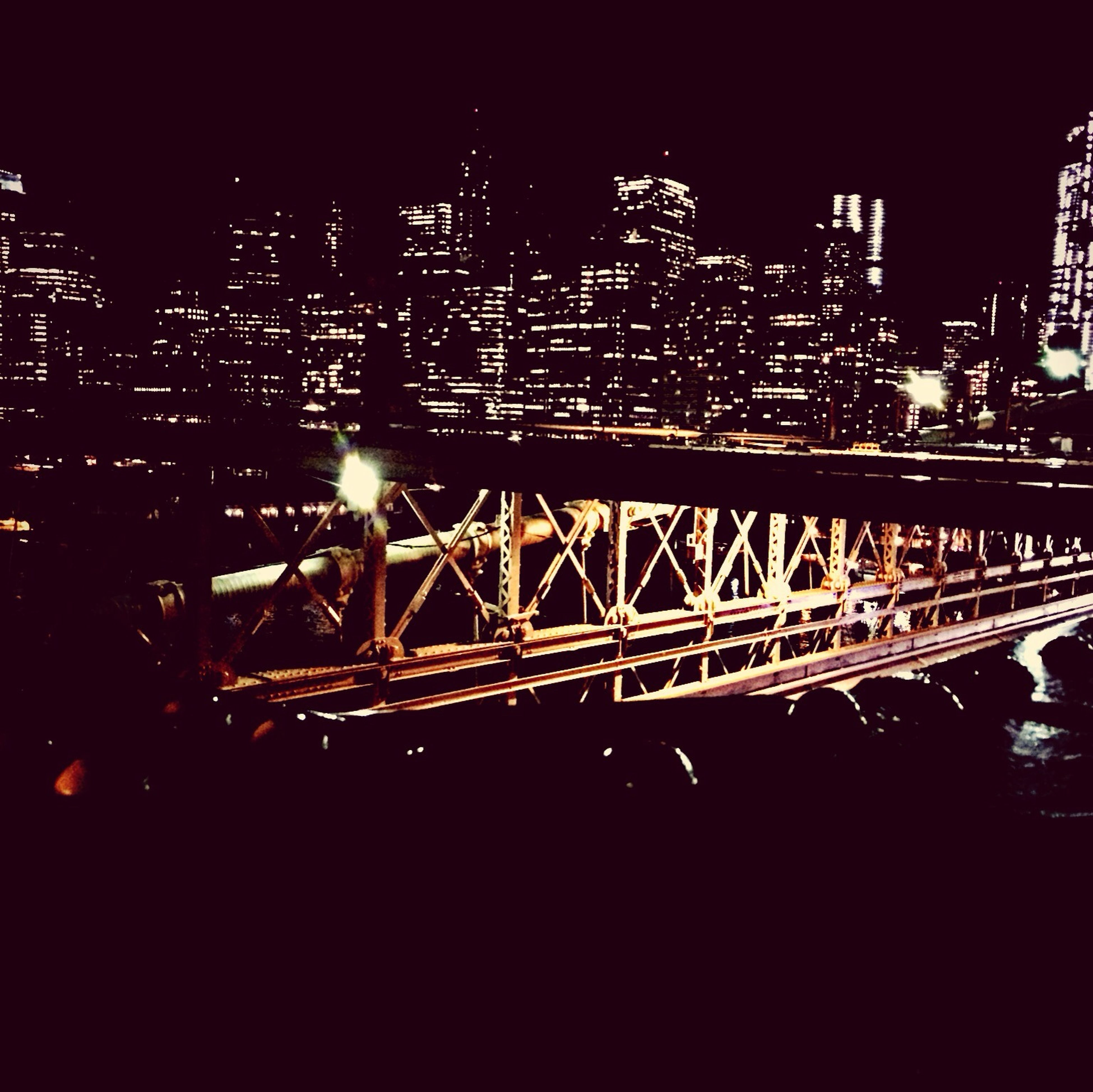 night, illuminated, architecture, city, built structure, building exterior, skyscraper, cityscape, modern, bridge - man made structure, transportation, connection, capital cities, tall - high, tower, city life, office building, engineering, travel destinations, urban skyline