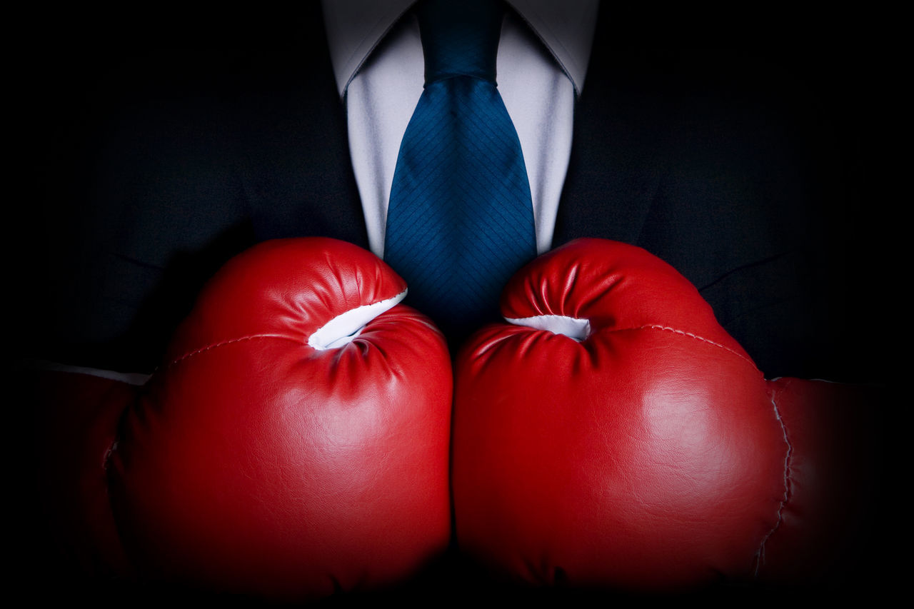 Business person wearing business suit and boxing gloves Boxing Gloves Business Person Businessman Conflict Executive  Fight Lawyer Male Man Manager People Red Sales Tough Toughness Winning