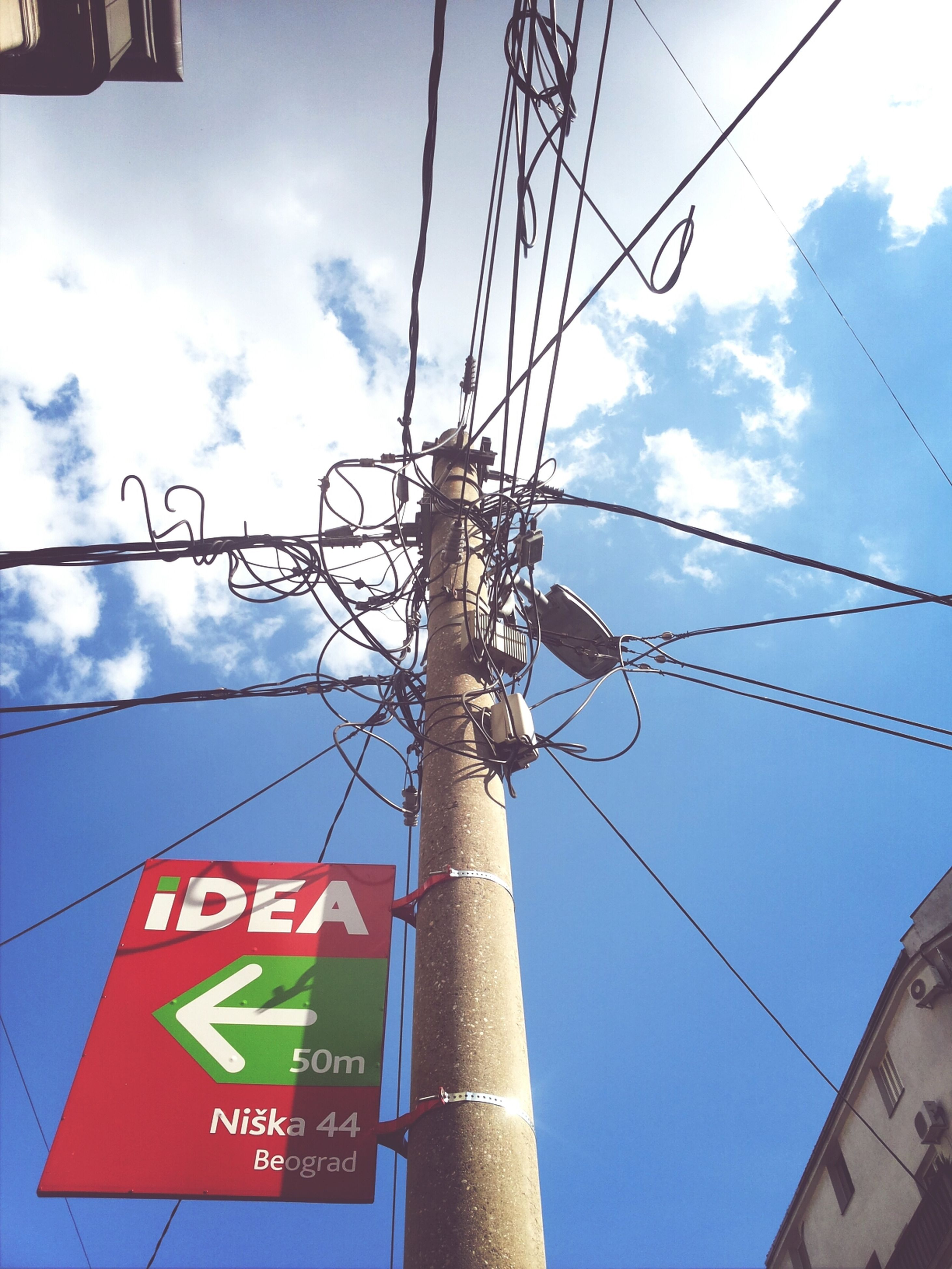 low angle view, sky, power line, cable, communication, power supply, electricity, electricity pylon, fuel and power generation, text, connection, pole, technology, western script, built structure, cloud - sky, architecture, cloud, day, cloudy