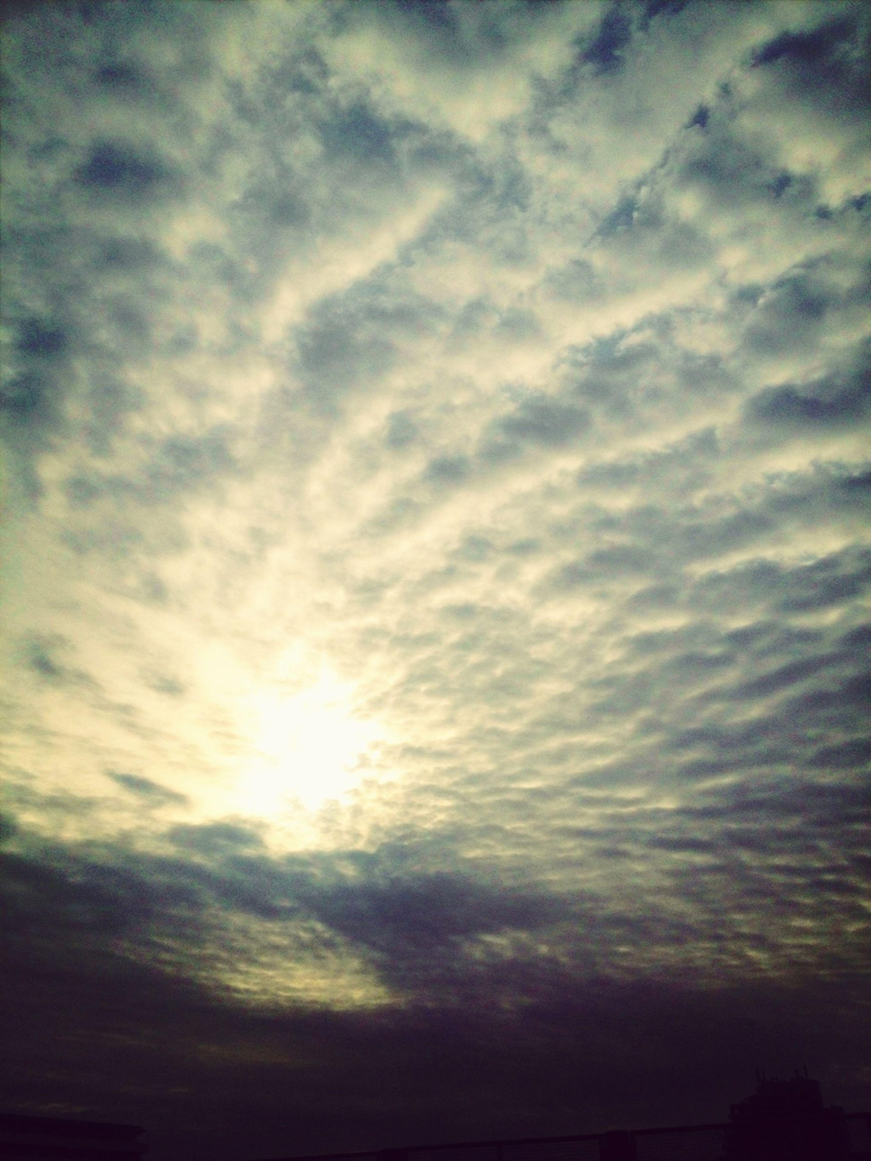 sky, cloud - sky, beauty in nature, scenics, sun, tranquility, sunset, tranquil scene, cloudy, nature, sunbeam, low angle view, cloud, cloudscape, sunlight, idyllic, silhouette, weather, outdoors, no people