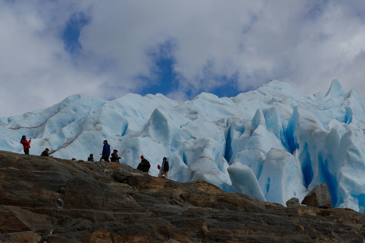 sky, nature, cloud - sky, cold temperature, winter, real people, beauty in nature, leisure activity, weather, adventure, mountain, scenics, lifestyles, day, outdoors, men, low angle view, physical geography, snow, women, landscape, glacier, large group of people, vacations, warm clothing, glacial, people