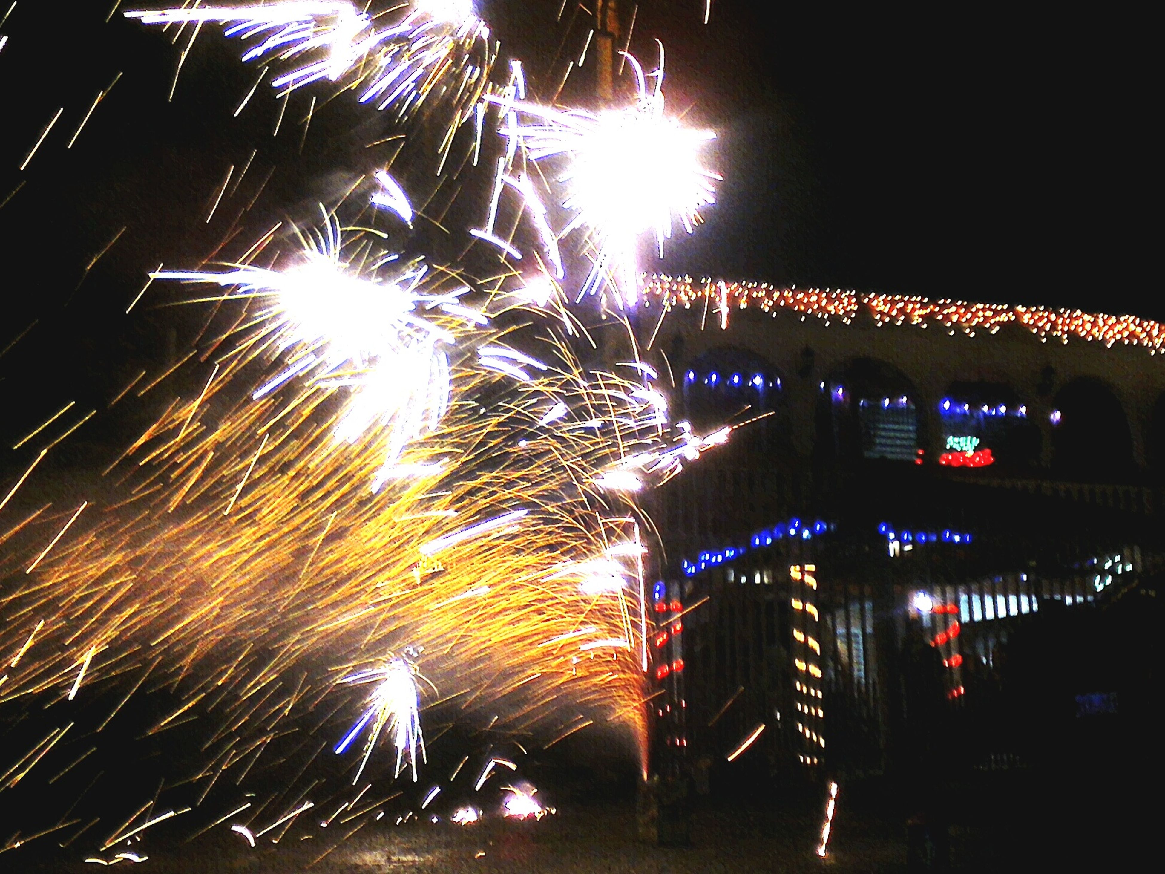 night, illuminated, glowing, long exposure, lighting equipment, built structure, architecture, building exterior, street light, firework display, celebration, motion, city, light - natural phenomenon, exploding, low angle view, dark, firework - man made object, outdoors, sky