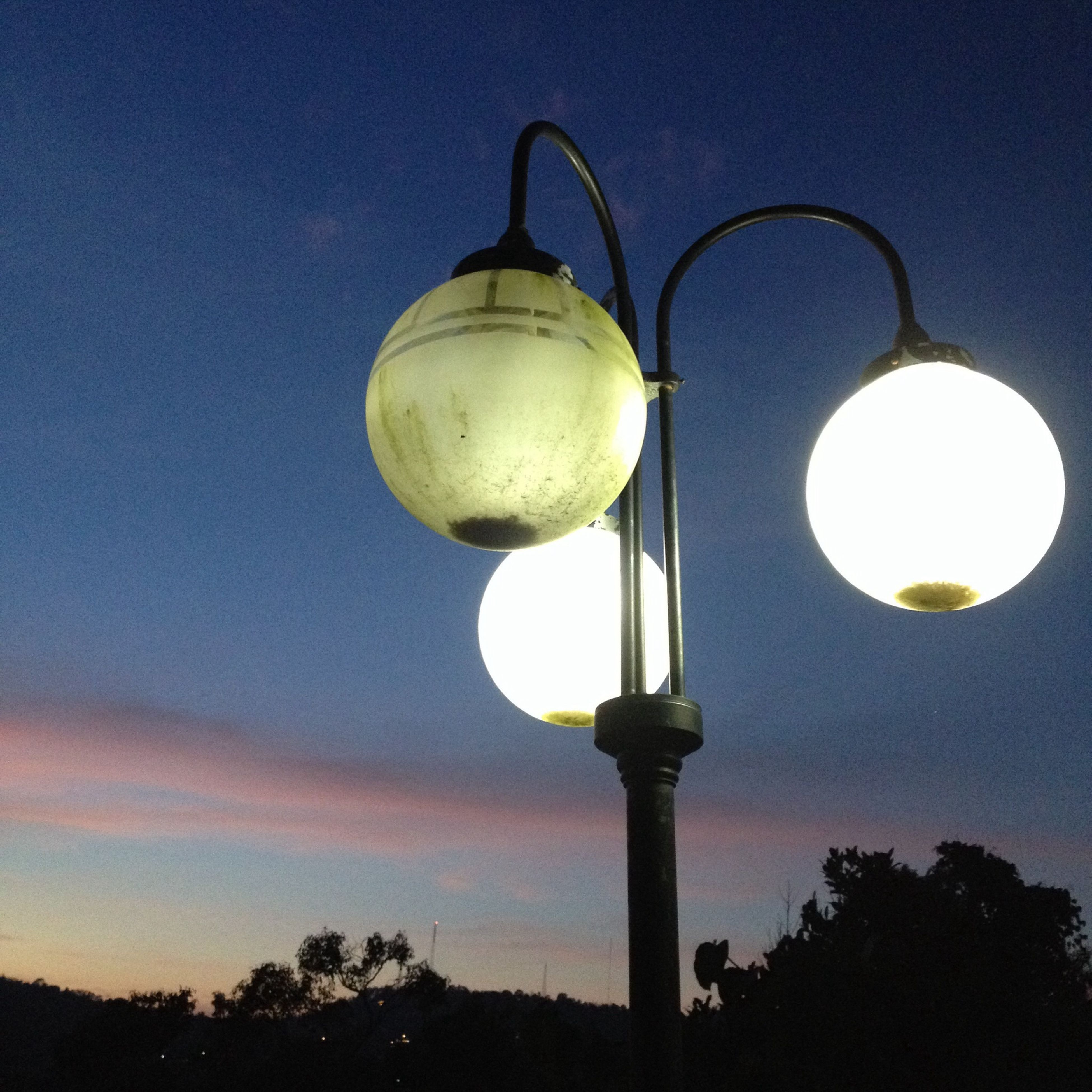 low angle view, lighting equipment, street light, illuminated, sky, electricity, electric light, sphere, tree, night, silhouette, hanging, light bulb, lamp post, moon, dusk, electric lamp, no people, outdoors, nature
