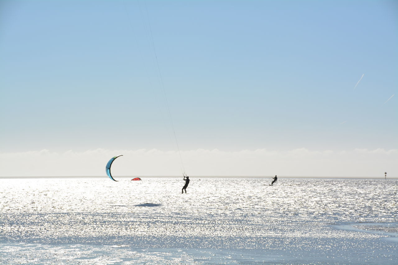 People Kiteboarding At Sea Against Sky