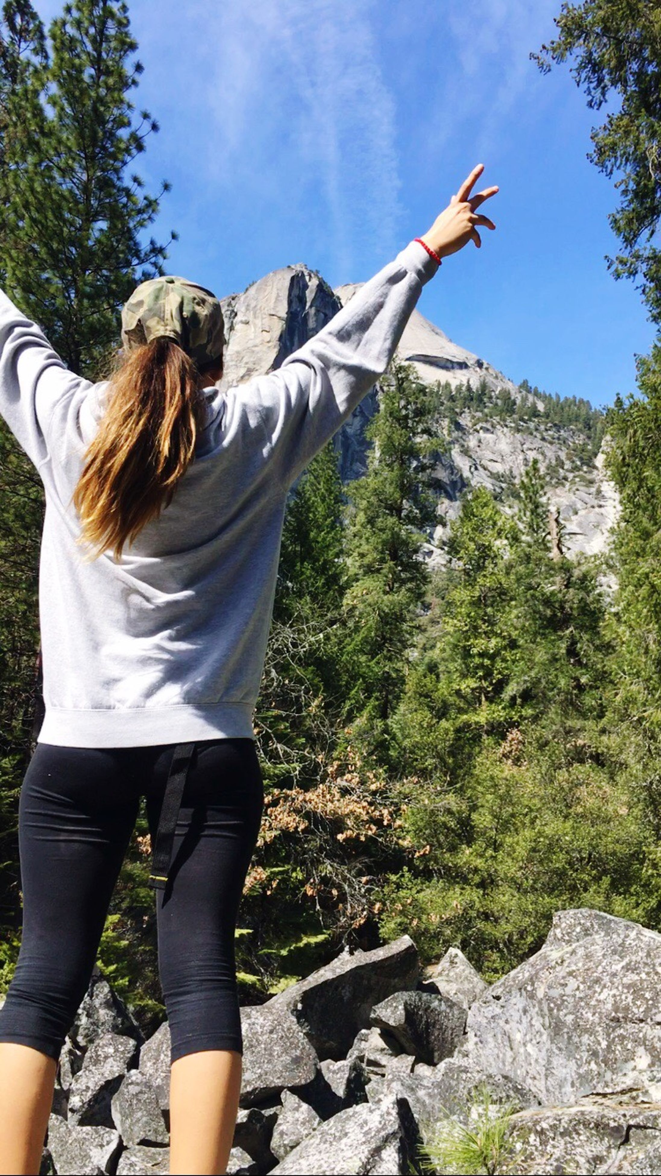 lifestyles, tree, casual clothing, leisure activity, standing, young adult, rear view, full length, sky, person, mountain, nature, men, day, rock - object, young women, low angle view, sunlight
