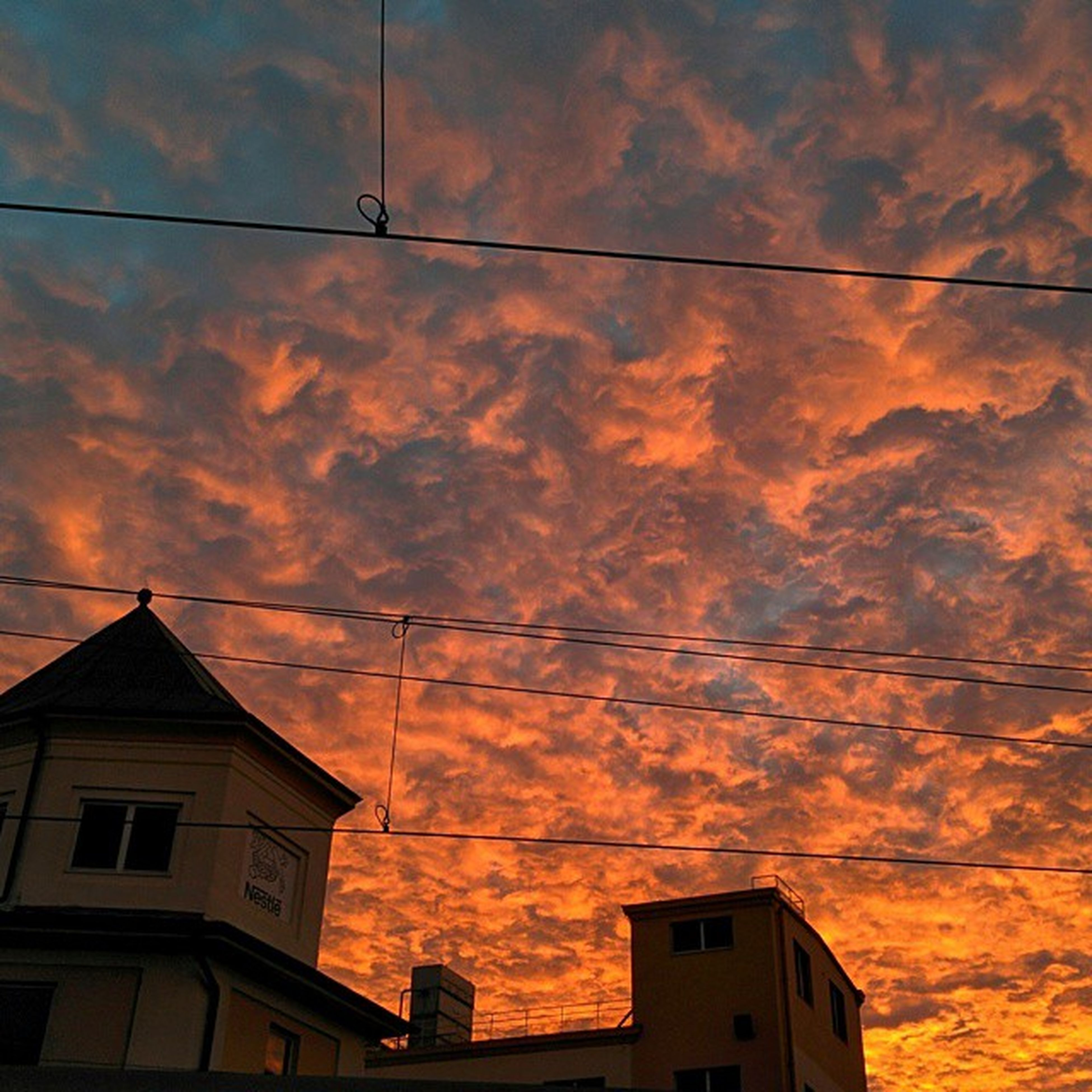 architecture, building exterior, built structure, low angle view, sunset, sky, cloud - sky, orange color, house, power line, high section, residential structure, cloudy, cloud, residential building, silhouette, building, cable, outdoors, no people