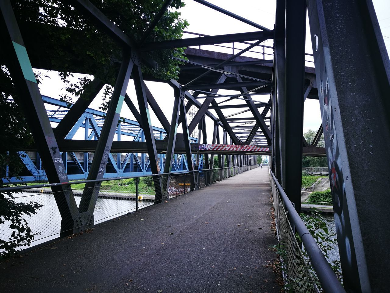 bridge - man made structure, connection, transportation, engineering, built structure, architecture, the way forward, road, day, diminishing perspective, bridge, covered bridge, metal, outdoors, railroad bridge, no people, girder, tree, footbridge, city, underneath, nature, sky
