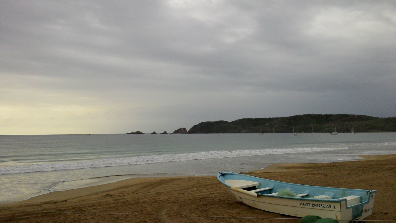 Boat Moored In Beach Against Cloudy Sky