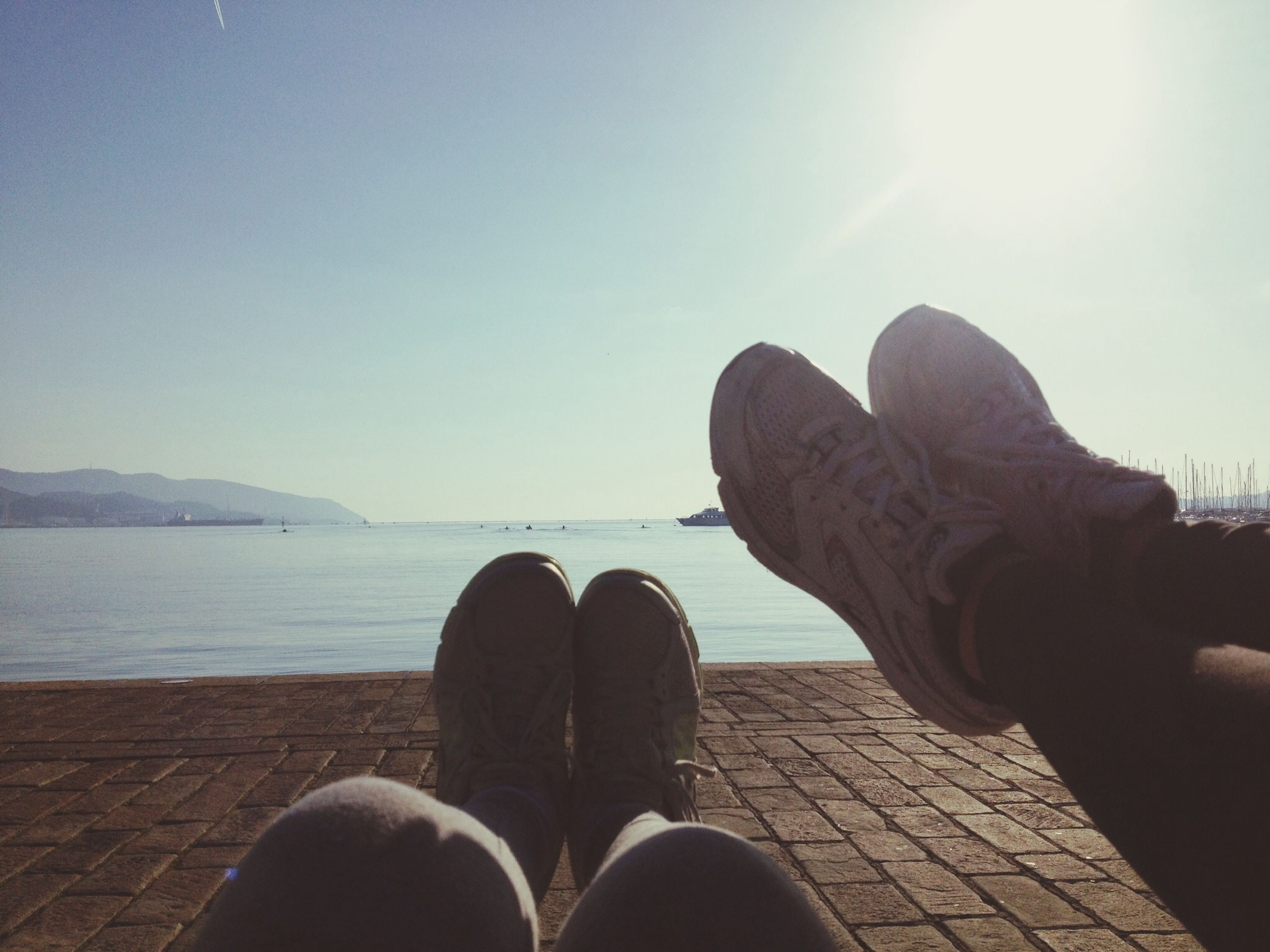 low section, personal perspective, person, shoe, water, sunlight, sky, part of, human foot, unrecognizable person, sea, lifestyles, clear sky, men, leisure activity, outdoors, day
