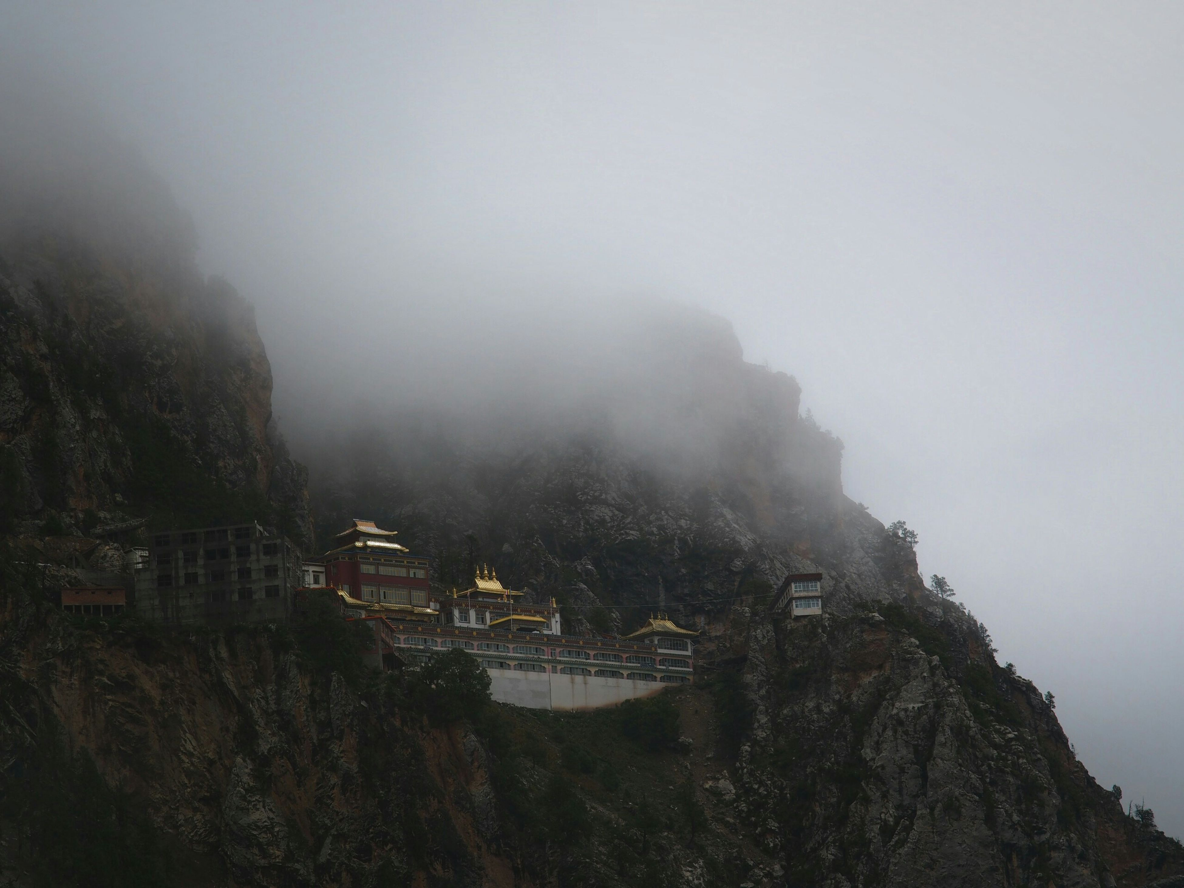 fog, foggy, weather, building exterior, built structure, architecture, mountain, house, high angle view, winter, landscape, sky, nature, residential structure, scenics, beauty in nature, copy space, tranquility, cold temperature, overcast