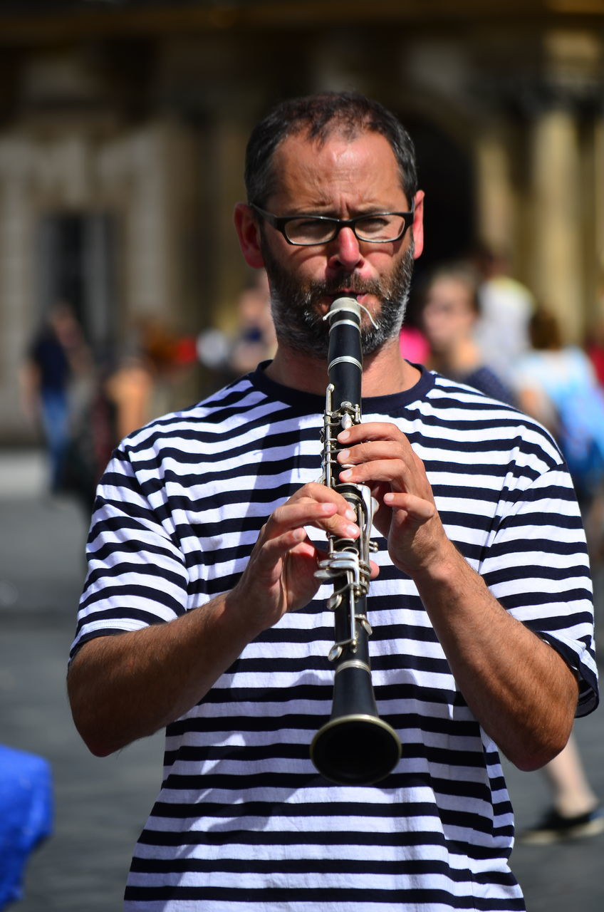 striped, musical instrument, music, real people, focus on foreground, one person, eyeglasses, front view, casual clothing, leisure activity, mature men, standing, playing, skill, day, lifestyles, arts culture and entertainment, outdoors, musician, performance, men, saxophone, close-up